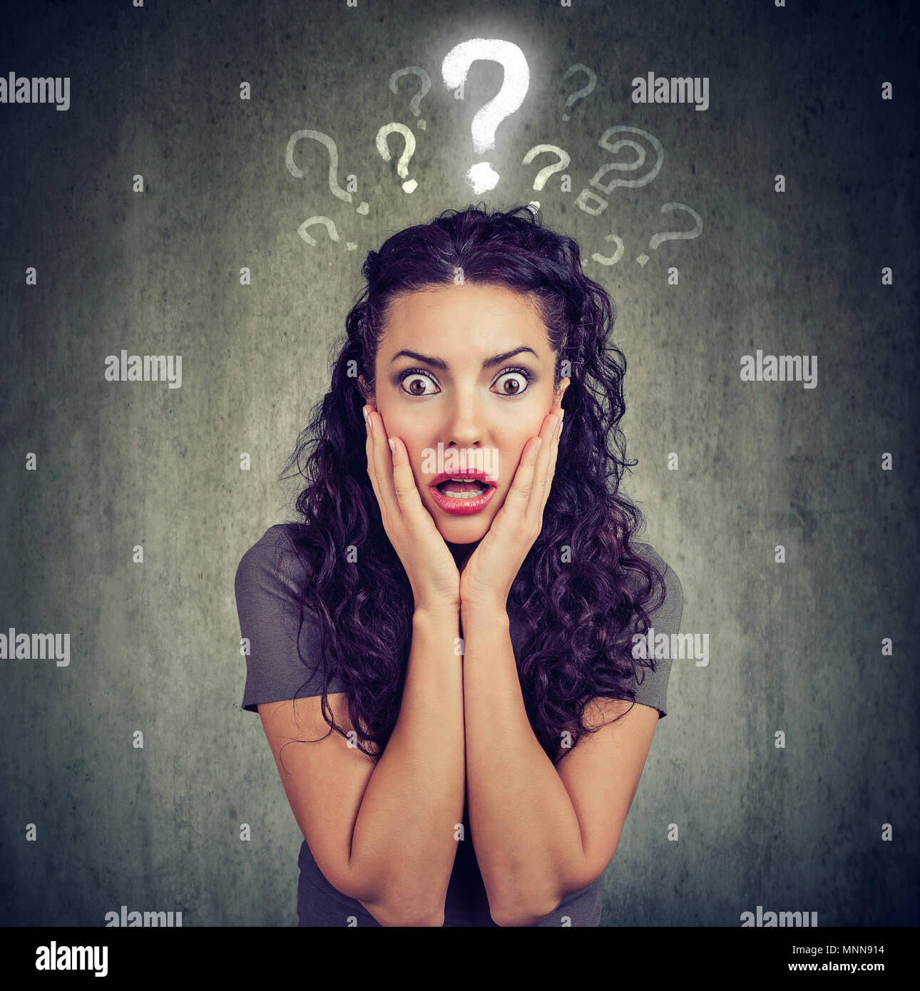 Shocked scared young woman looking at camera has many questions - Stock Image