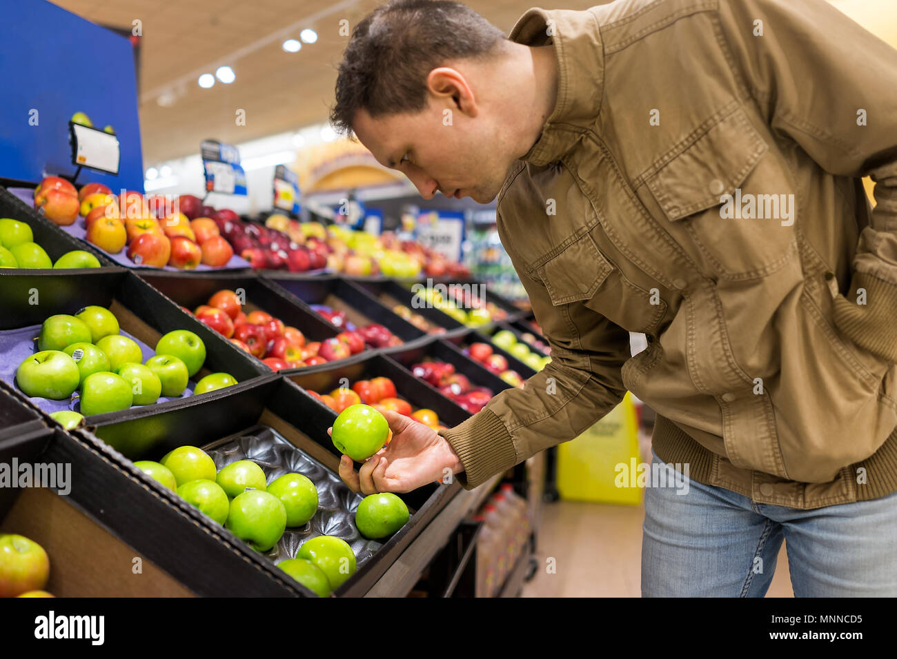 Many varieties assorted apples on display shelf in grocery store boxes in aisle, supermarket inside, man person customer holding choosing granny smith - Stock Image