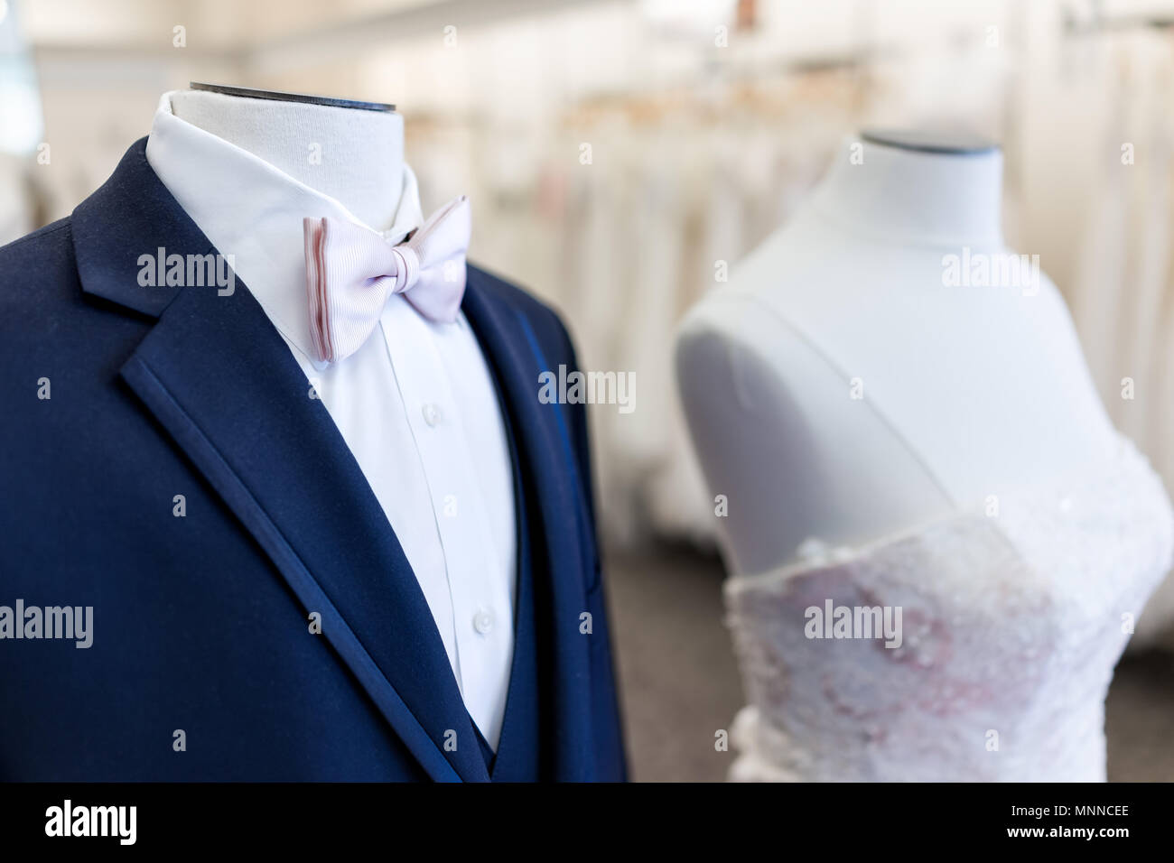 Closeup of bride and groom mannequin in blue, pink wedding attire suit, butterfly necktie, tie and white gown in boutique store, shop - Stock Image