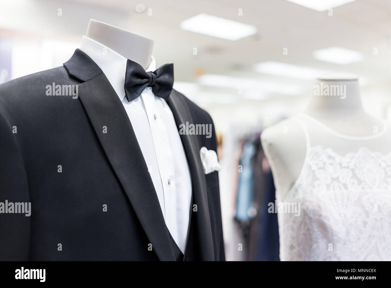 Closeup of bride and groom mannequin in black wedding attire suit, butterfly necktie, tie and white gown in boutique store, shop, handkerchief - Stock Image