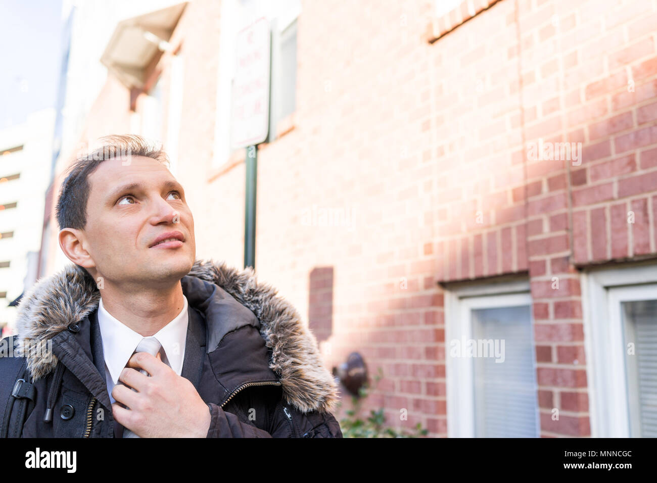 Handsome, attractive young serious happy businessman closeup face portrait standing in front of brick wall, fixing tie, in suit and tie on interview b - Stock Image