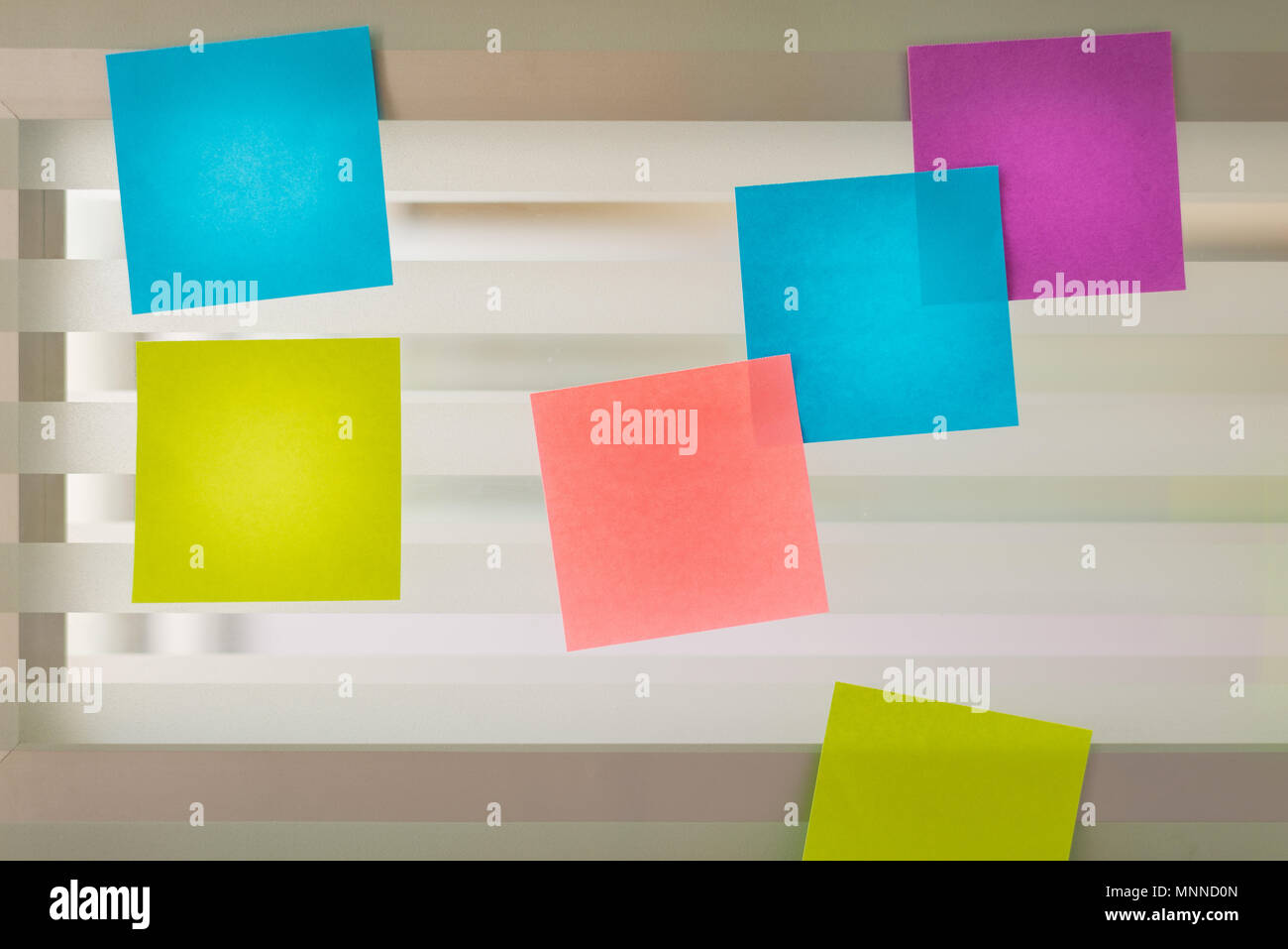 Randomly scattered colored sticky notes over glass screen of a bench desk - Stock Image