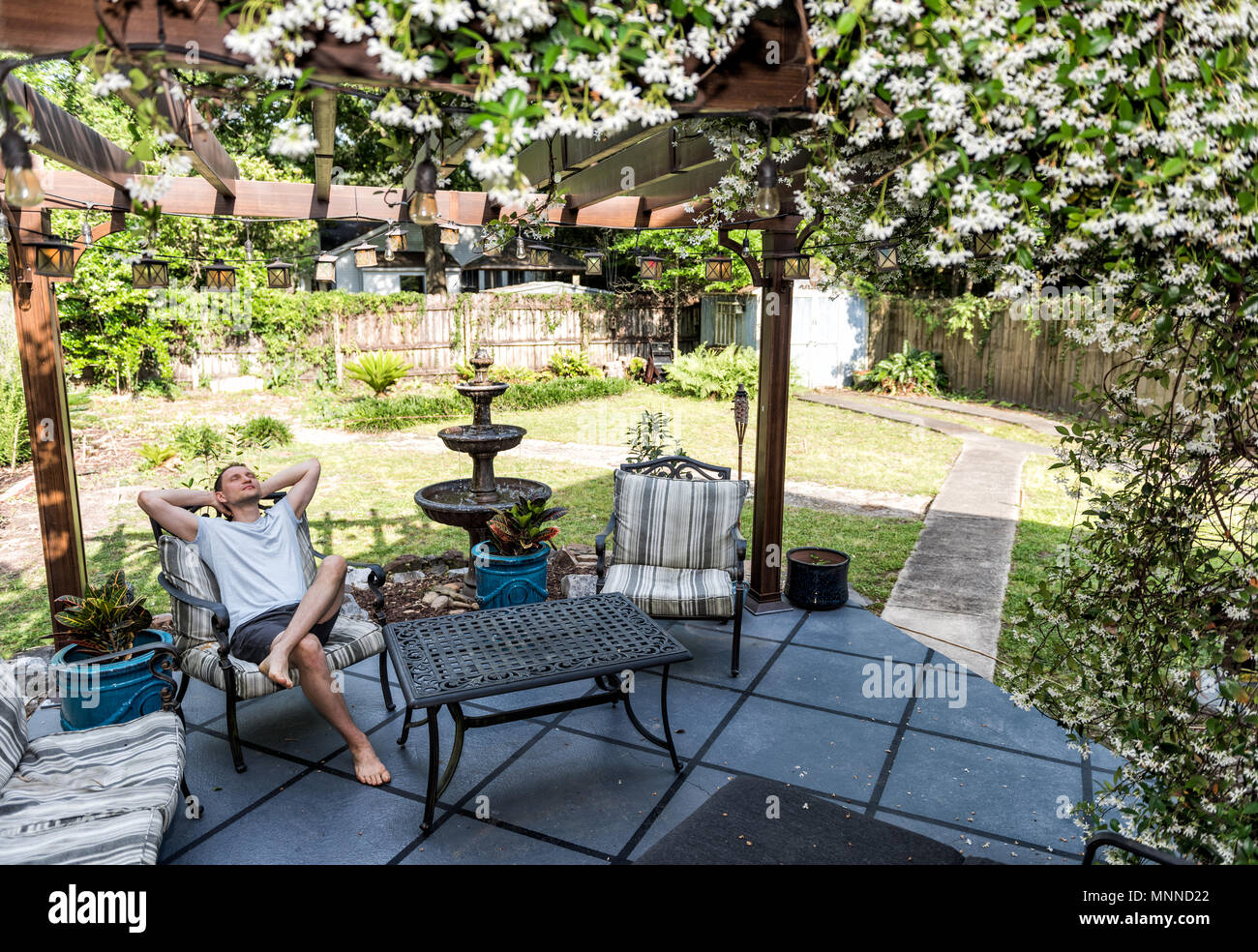 Young Man Lying Down On Patio Lounge Chair In Outdoor Spring Flower Garden  In Backyard Porch Of Home Happy Smiling In Zen With Fountain, Pergola Canop