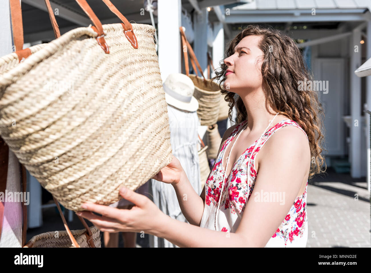 Closeup of young woman shopping for straw beach bag in outdoor market shop store in European, Greece, Italy, Mediterranean town, village in colorful s - Stock Image