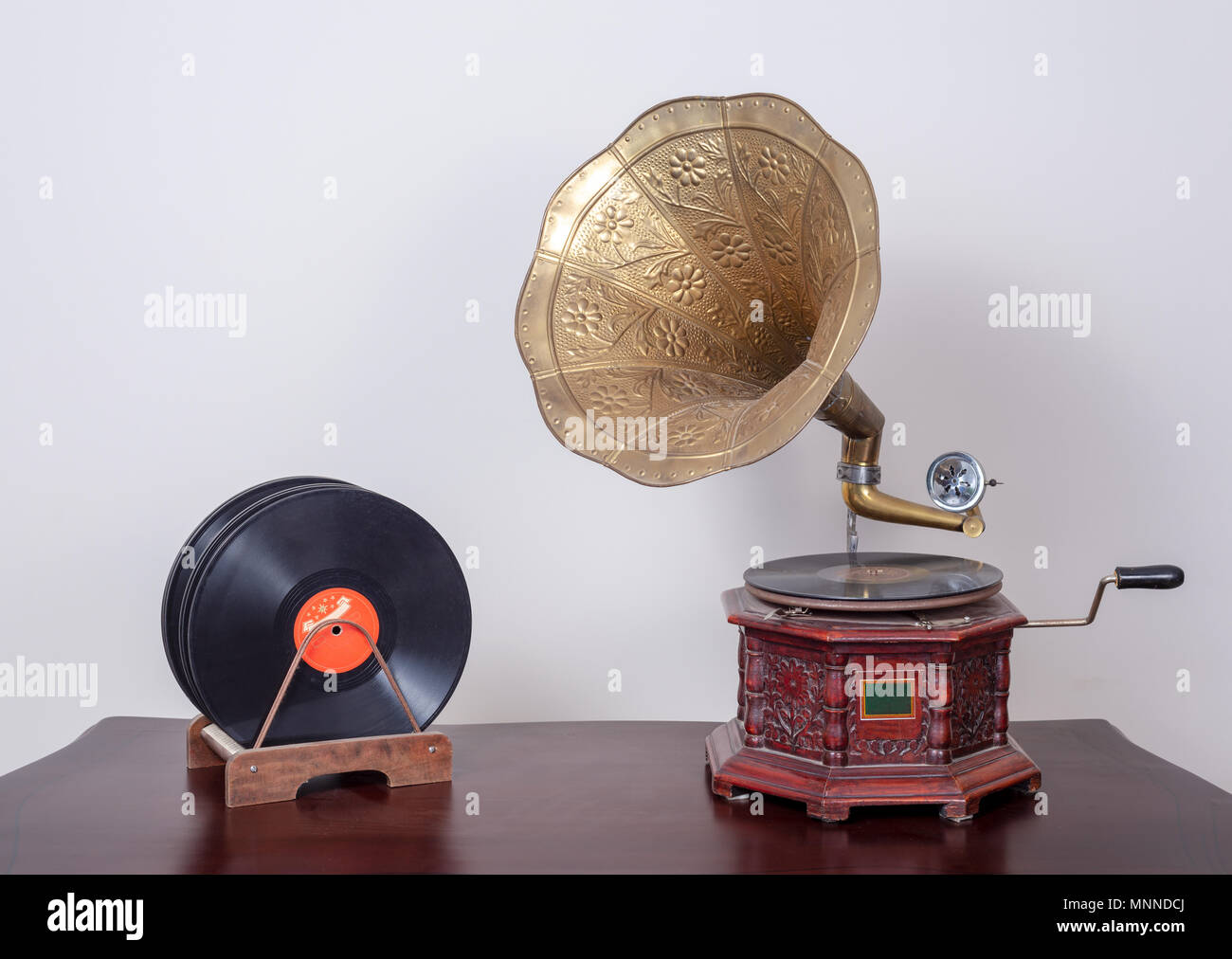 Still life of a nineteenth century phonograph (gramophone) and vinyl records on a wooden table and beige wall - Stock Image