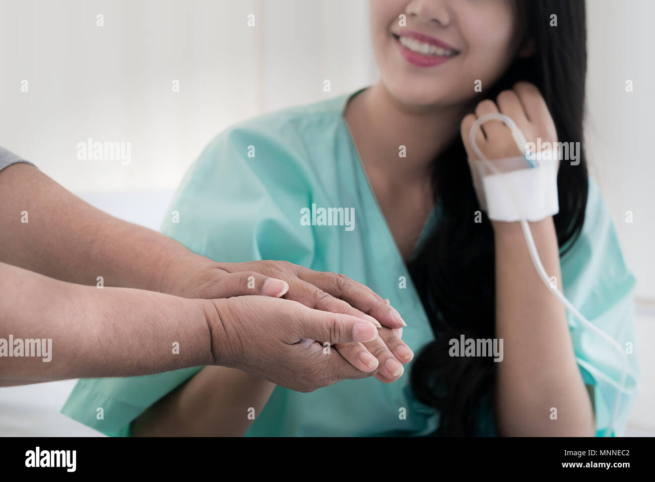 Mother hands holding her daughter patient hand sitting at the desk for encouragement, empathy, cheering and support while medical examination. Good ne - Stock Image