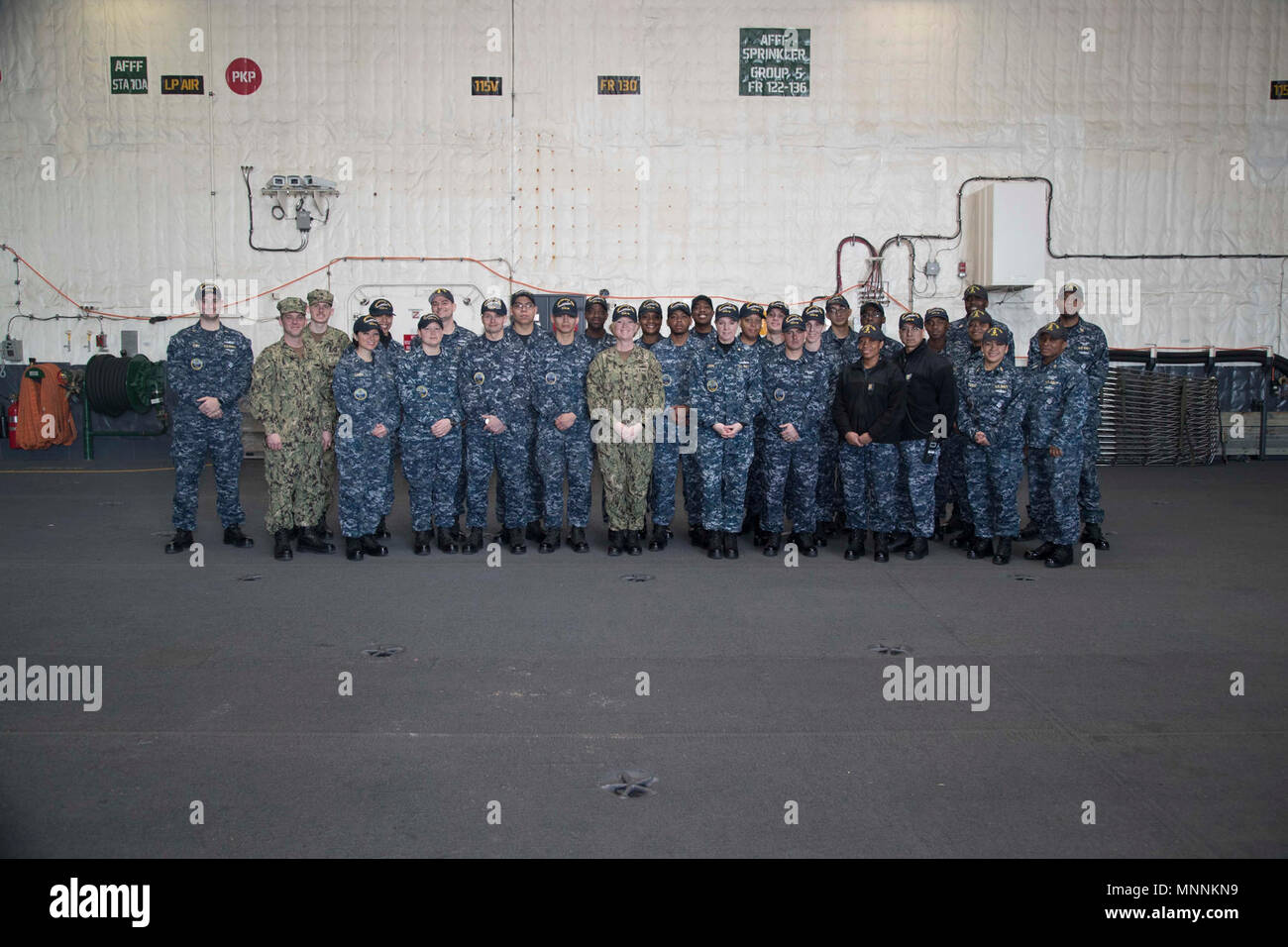 NORFOLK, Va. (Mar. 16, 2018) -- USS Gerald R. Ford's (CVN 78) administrative division, Lt. Cmdr. Melissa Chope, Ford's administrative officer, and Command Master Chief Laura Nunley pose for a photo after completing a uniform inspection for Division in the Spotlight. - Stock Image