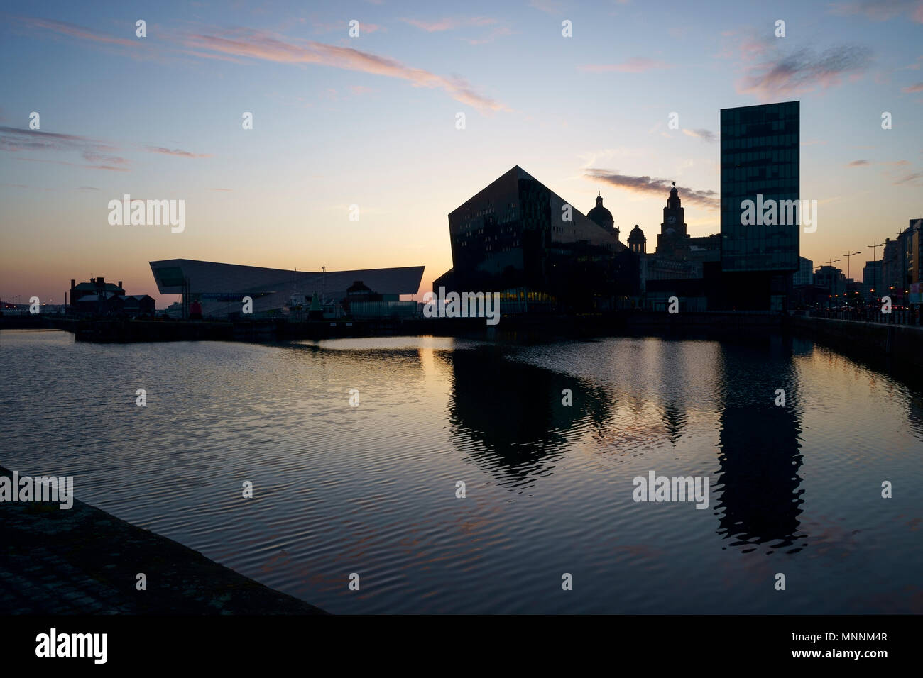 Evening dusk view across Canning Dock towards Mann Island and the Liver Building Liverpool UK - Stock Image