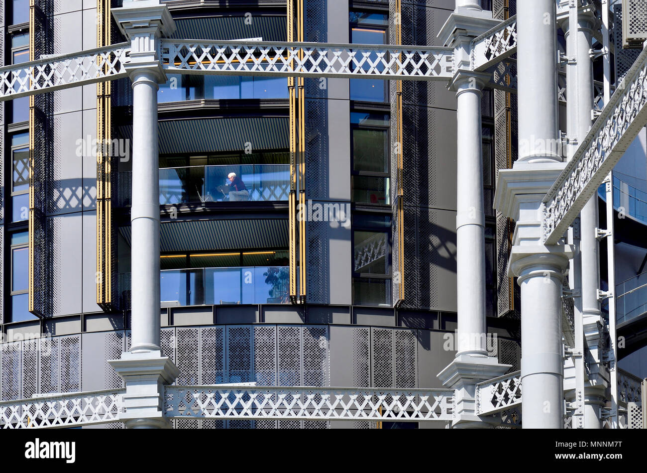 Gasholder Apartments, Lewis Cubitt Square, Kings Cross, London, England, UK. Luxury flats built in Grade II listed gasholders - man sitting on his bal - Stock Image