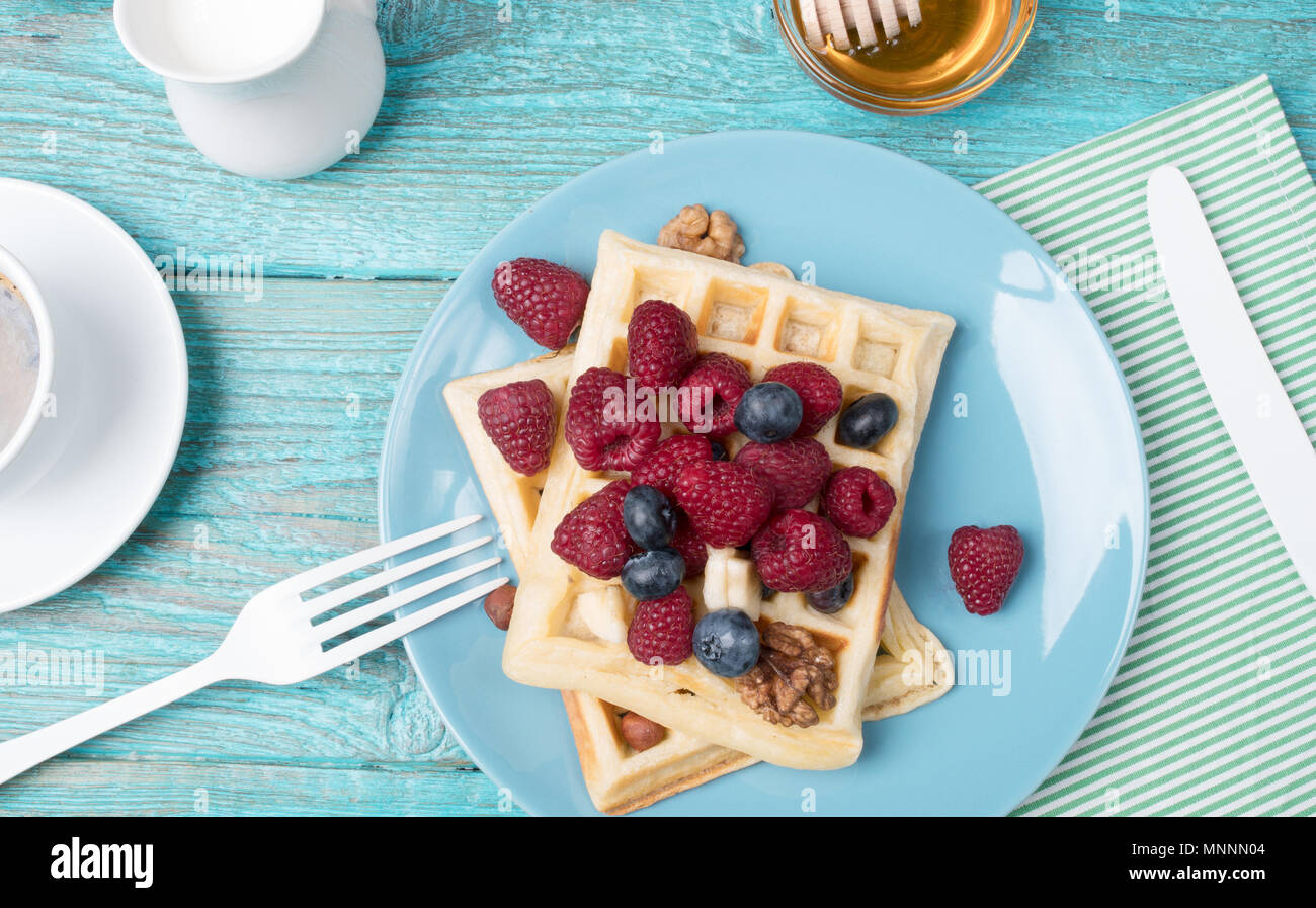 Homemade waffles with raspberries and blueberry, cup of coffee, milk and cutlery - Stock Image