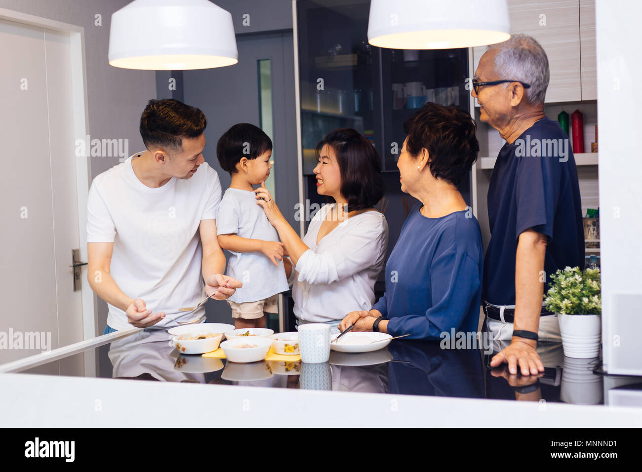 Happy Asian extended family preparing food at home full of laughter and happiness - Stock Image
