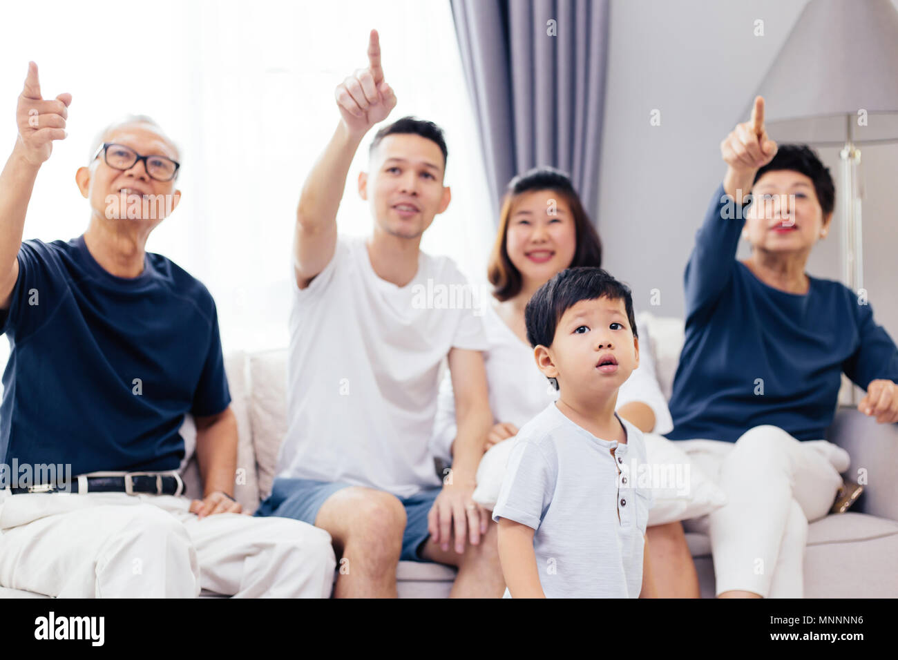 Asian extended family pointing out to something and the child is curious to look at it - Stock Image