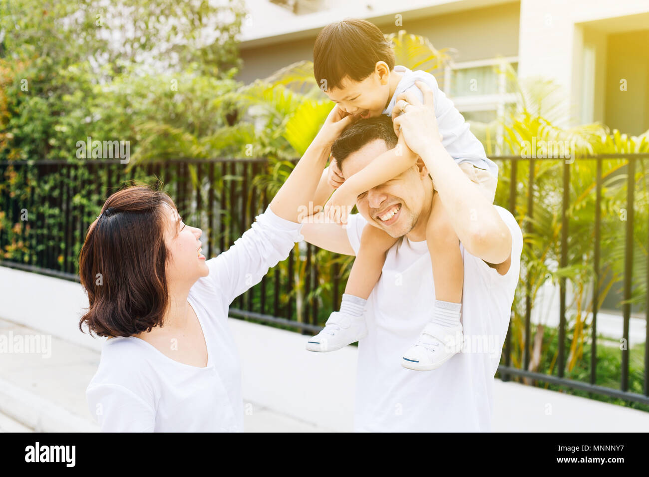 Cute Asian father piggybacking his son along with his wife in the park. Excited family spending time together with happiness - Stock Image