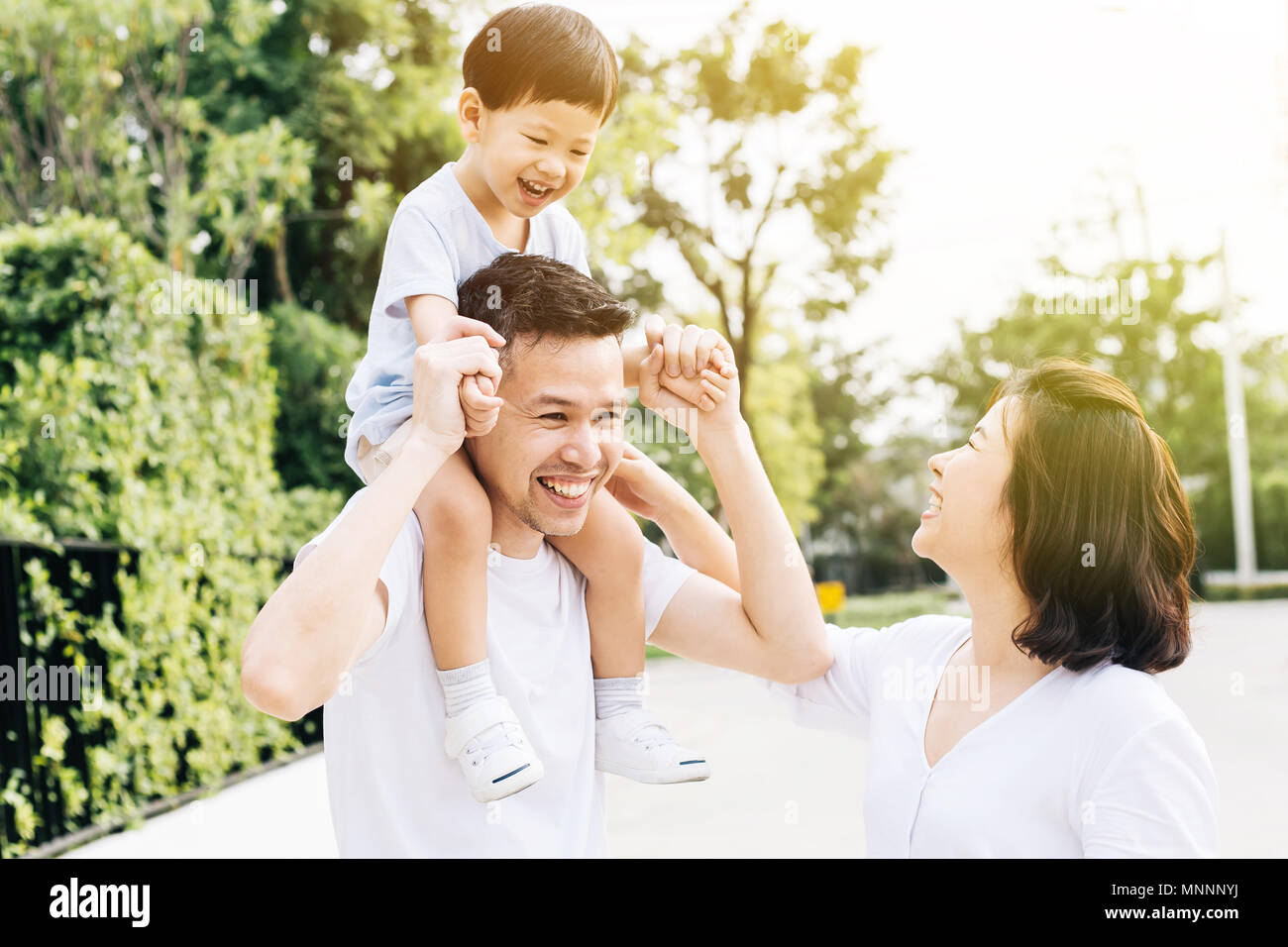 Cute Asian father piggbacking his son along with his wife in the park. Excited family spending time together with happiness - Stock Image