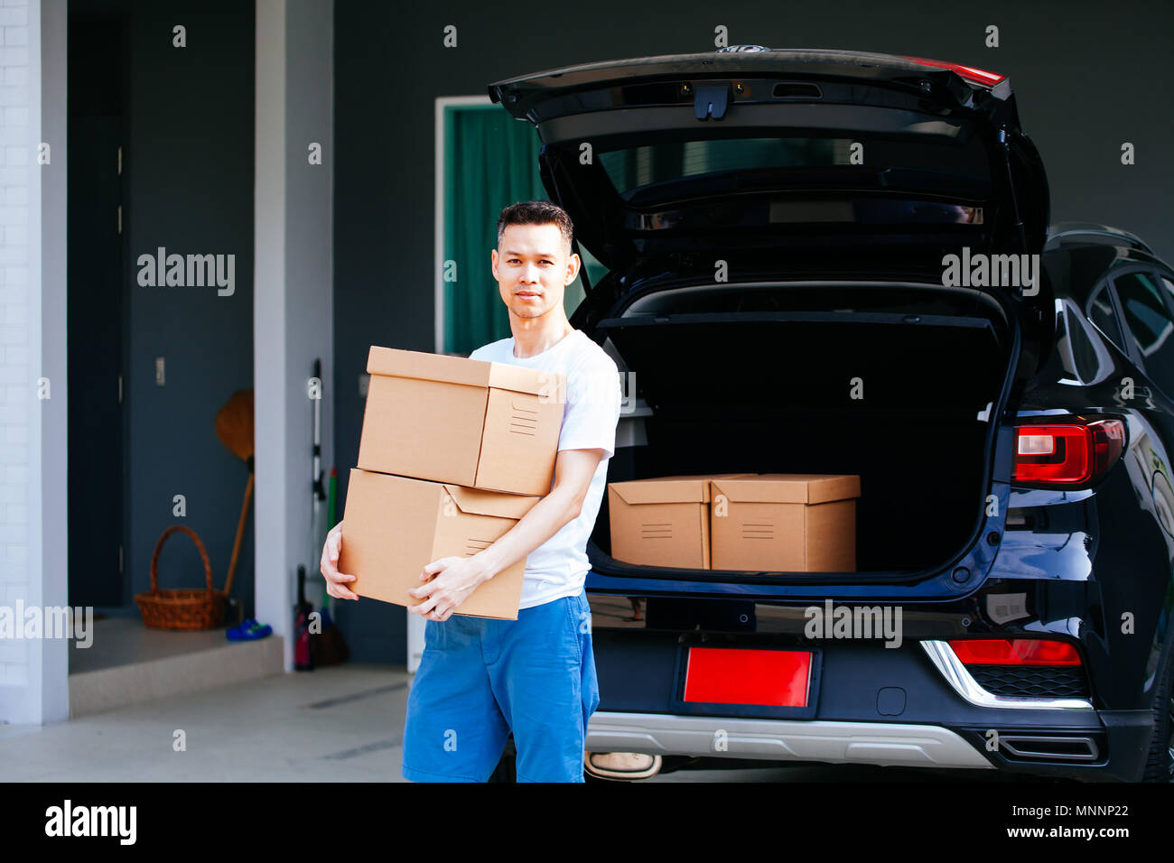 Mature Asian man carrying cardboard boxes from car trunk at new home - Stock Image