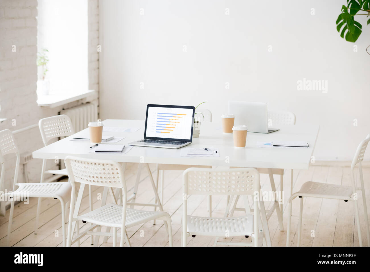 Meeting table with laptops and coffee in empty office room - Stock Image