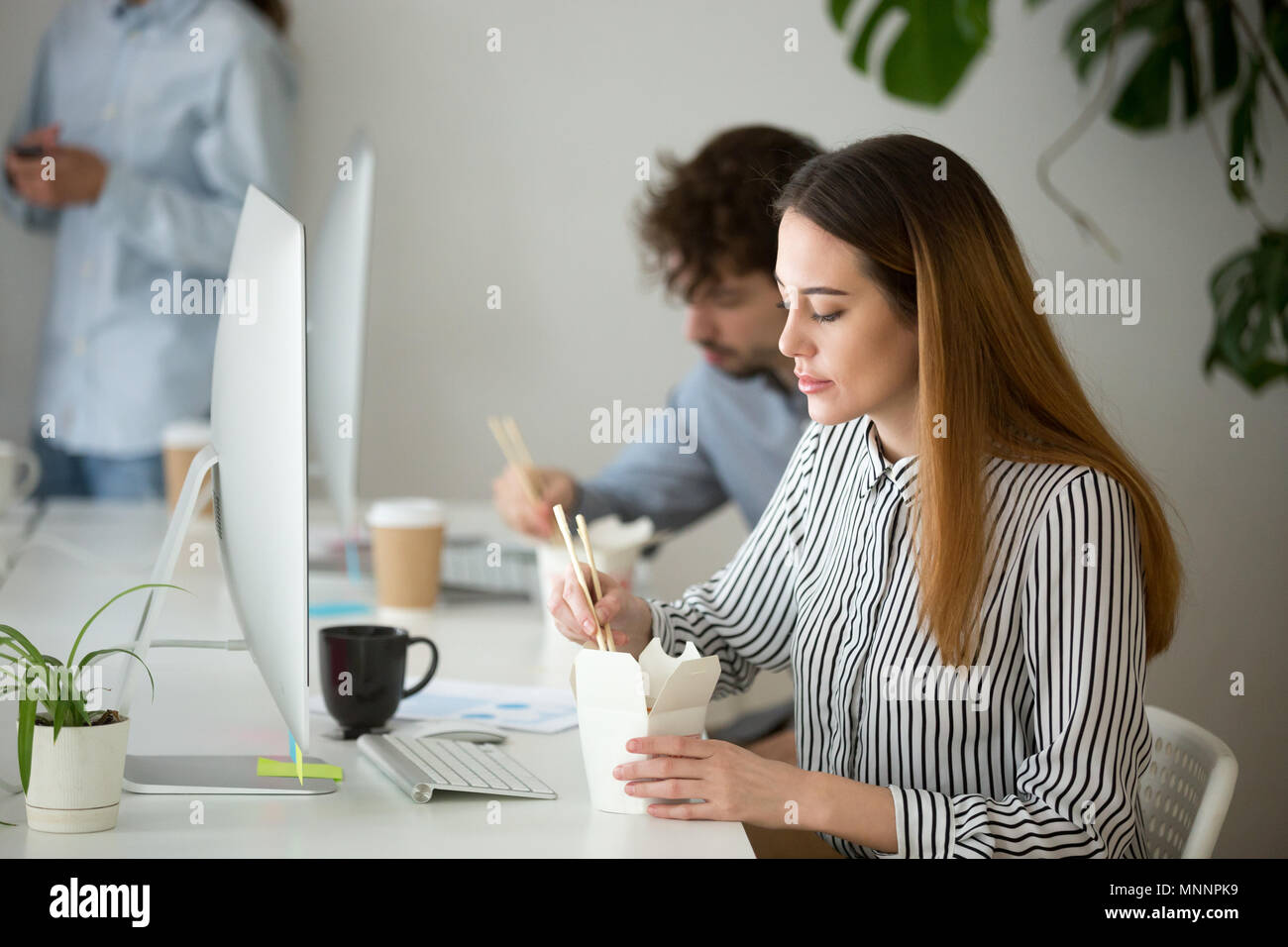 Young woman enjoying chinese food box during office lunch break - Stock Image