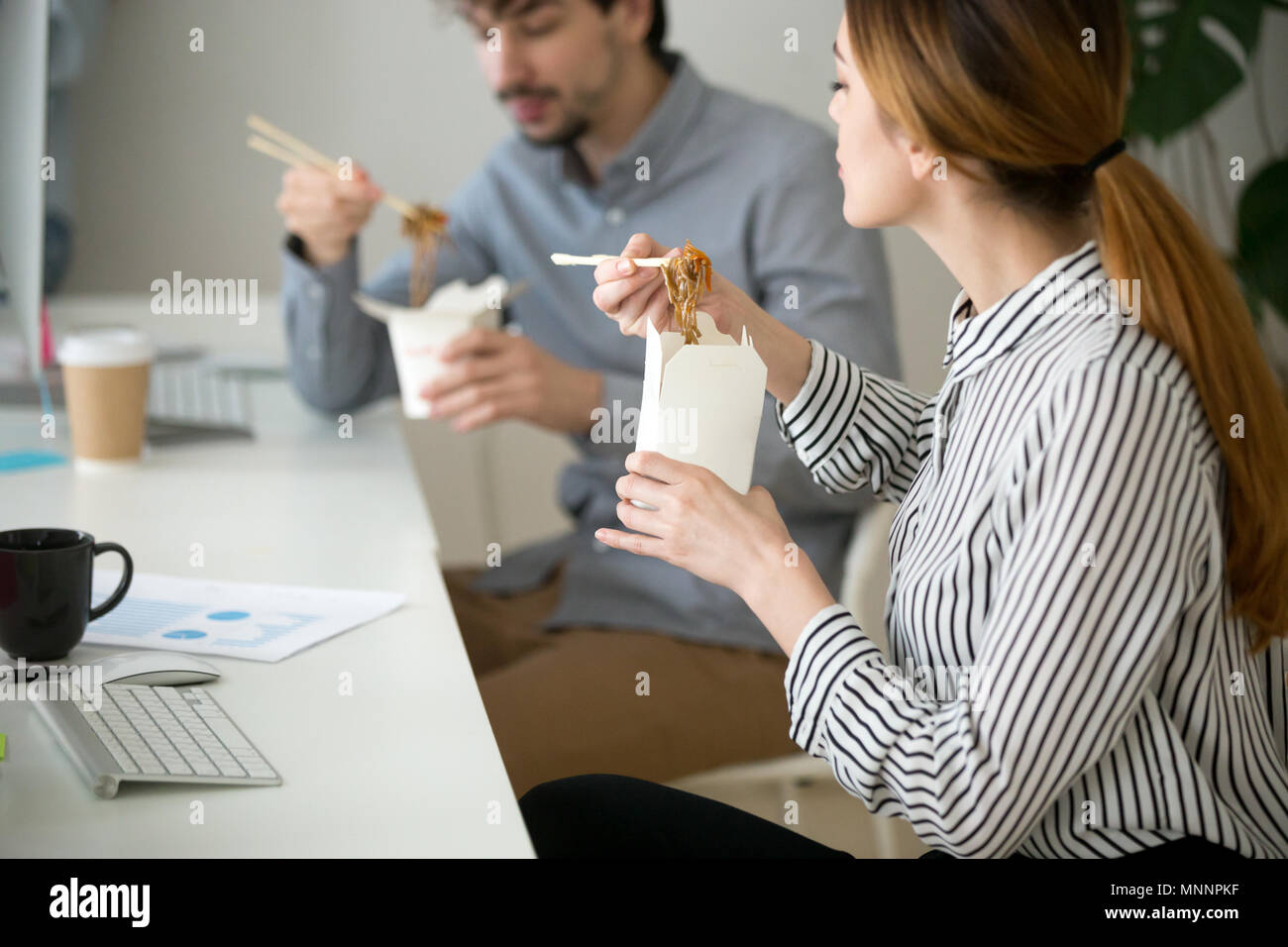 Office people eating chinese food in noodle box during lunch - Stock Image