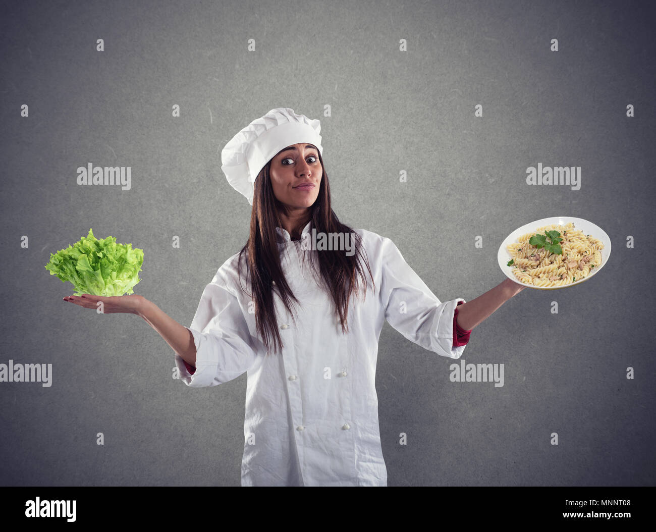 Chef undecided between fresh salad or pasta dish - Stock Image