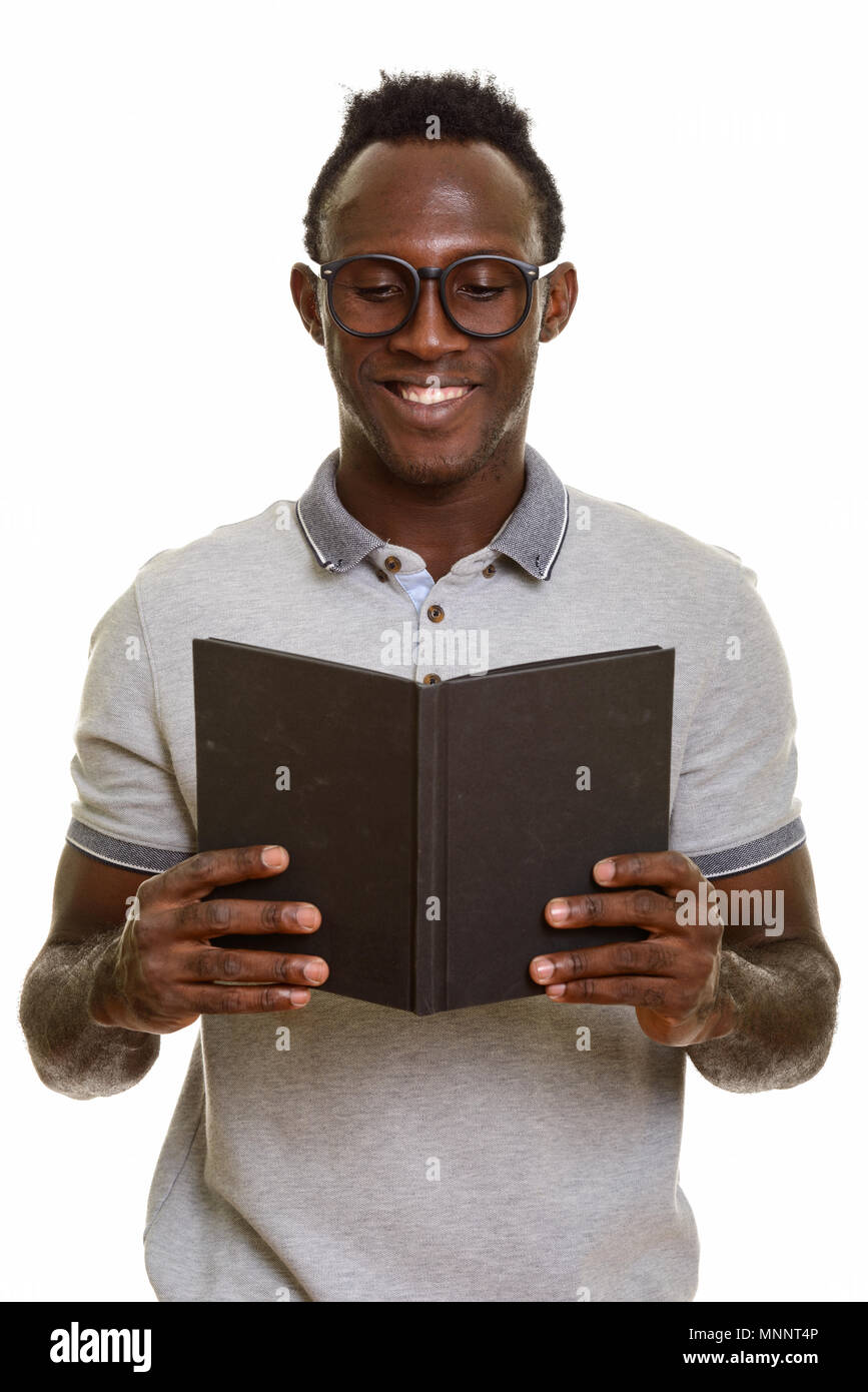Young happy African man smiling while reading book - Stock Image
