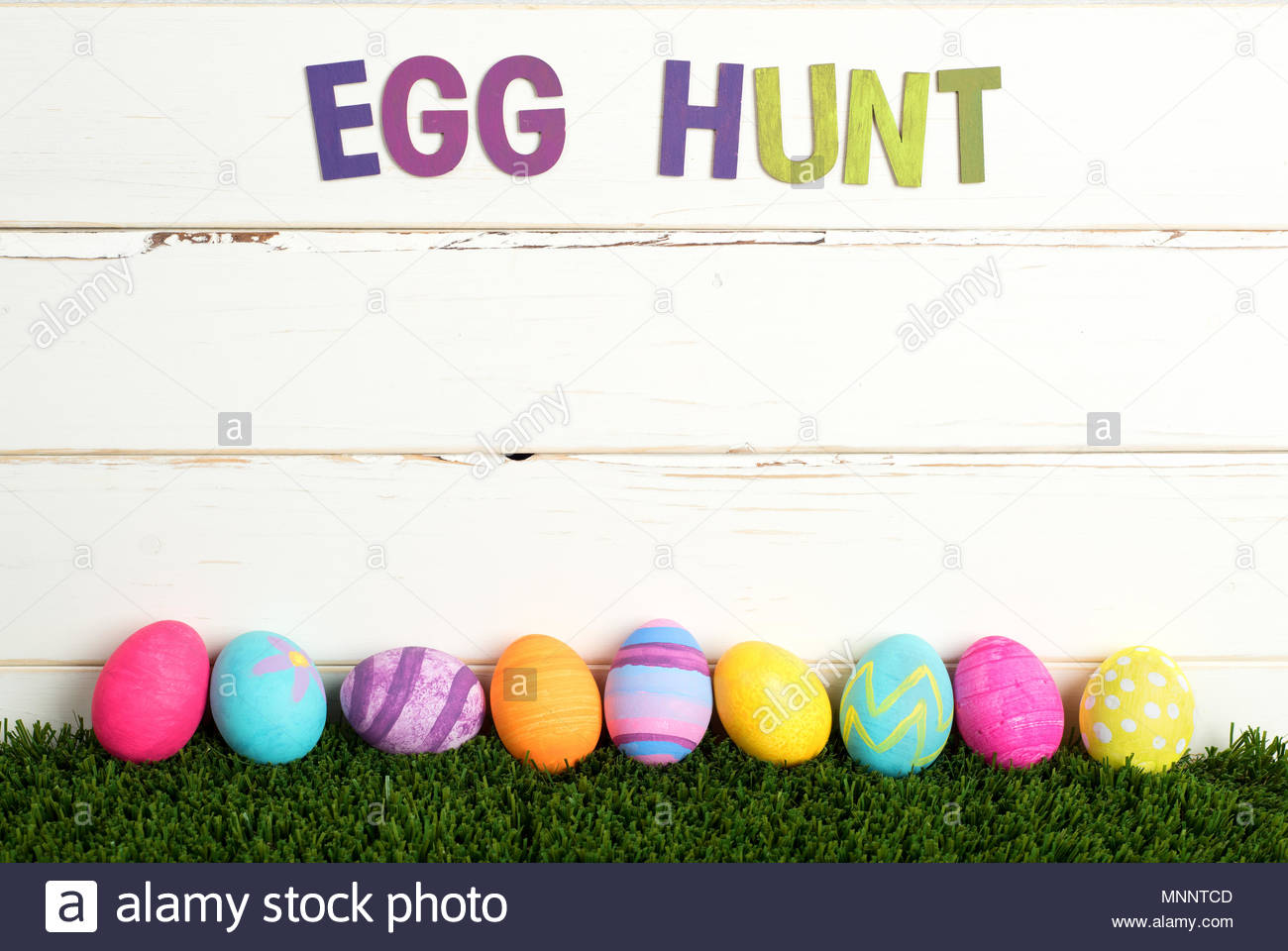 easter egg hunt invite with colorful dyed eggs in a line on grass and agasint white shiplap board background with room or space for your words copy