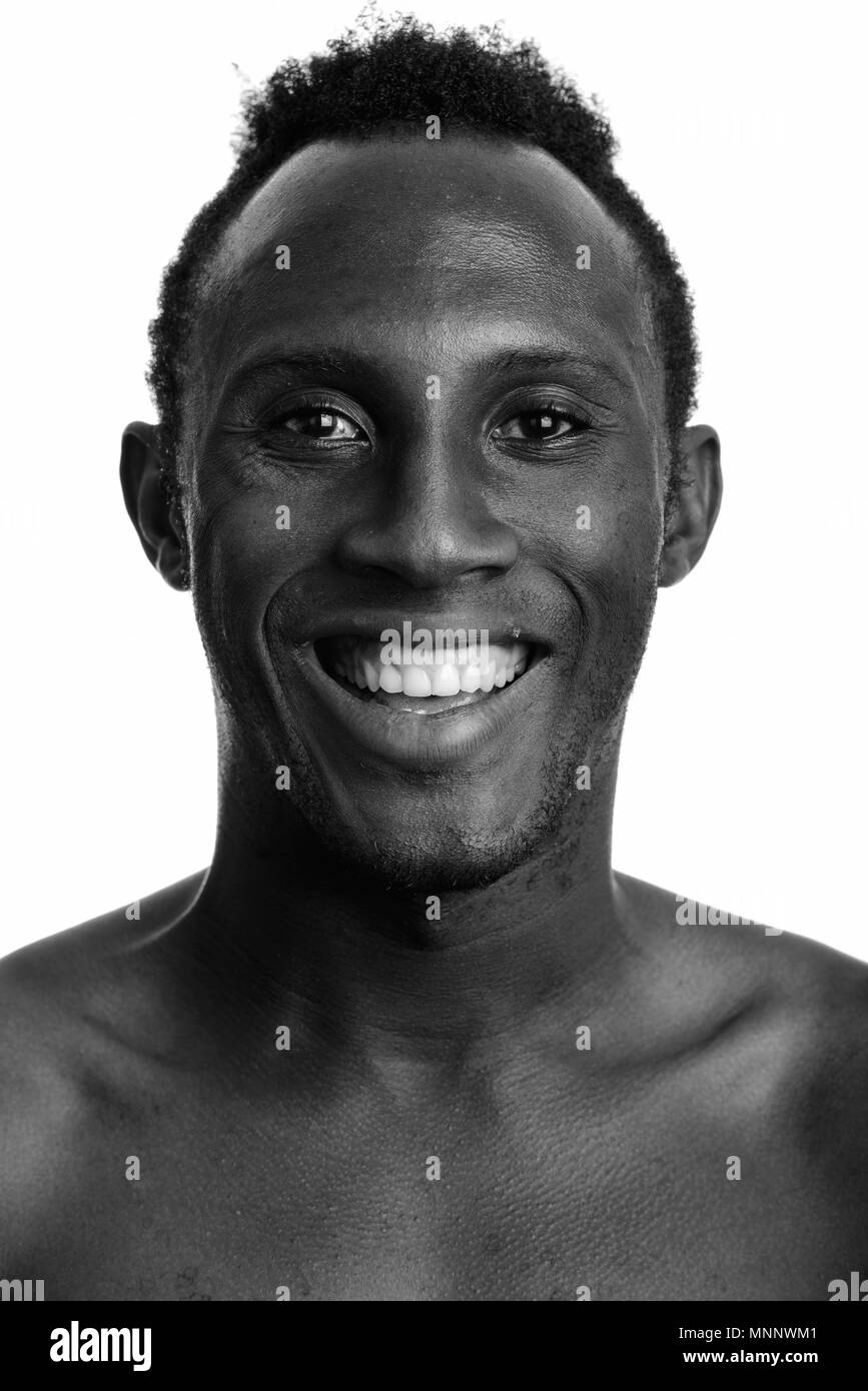 Face of young happy African man smiling in black and white - Stock Image
