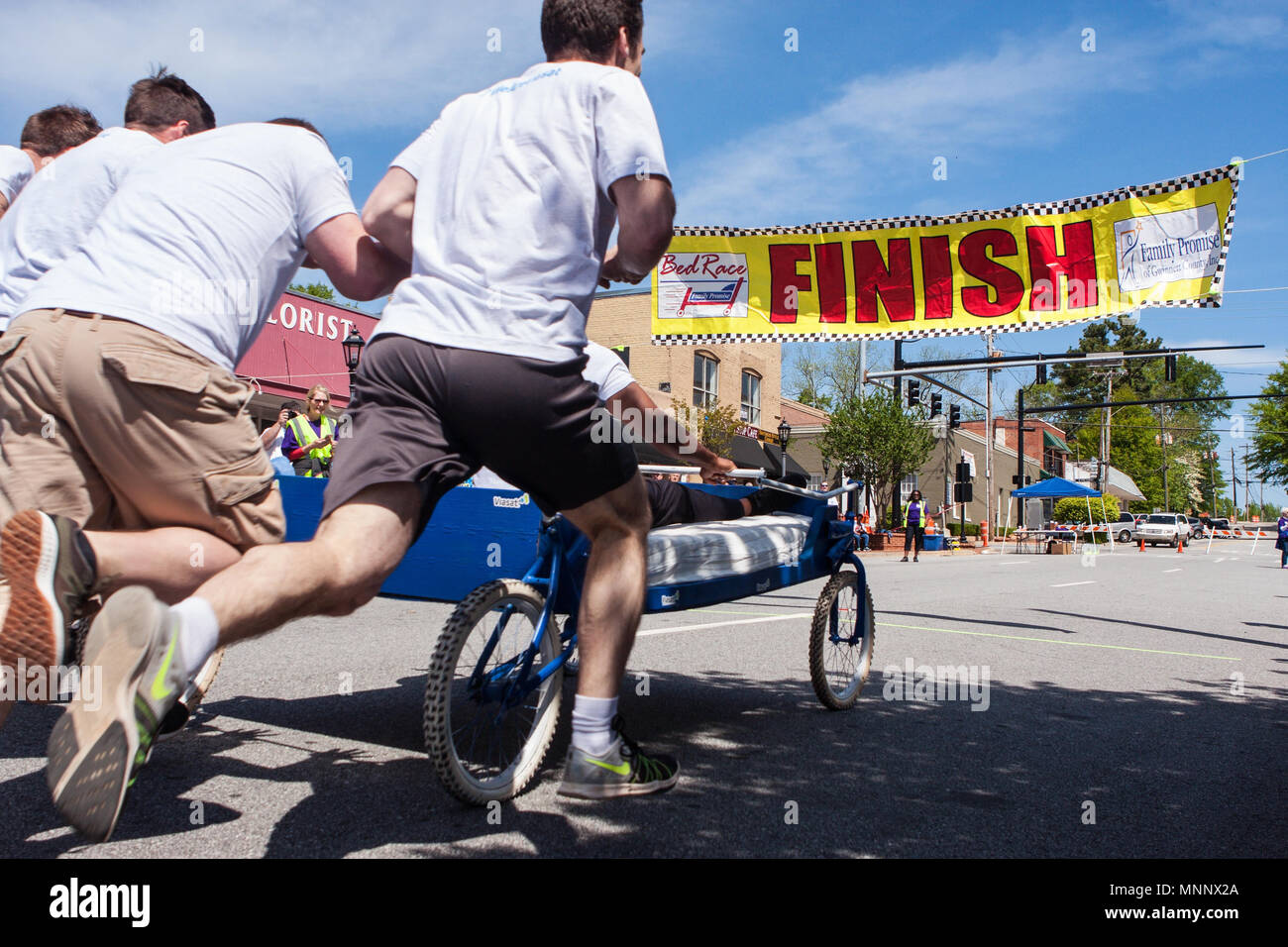 A team pushes a bed on wheels toward the finish line of a charity fundraiser event