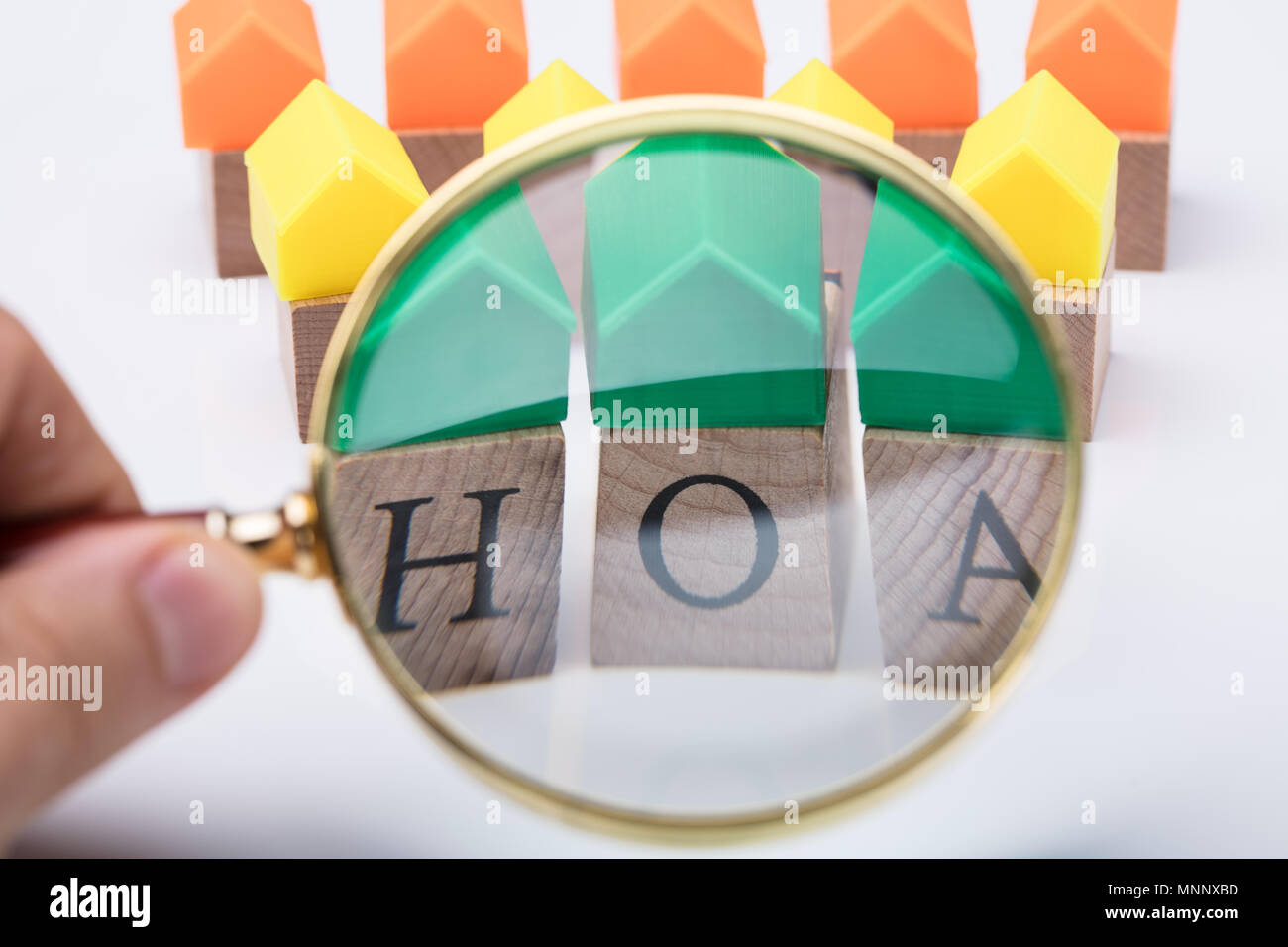 Green House Model Over Homeowner Association Wooden Blocks Seen Through A Person Holding Magnifying Glass - Stock Image