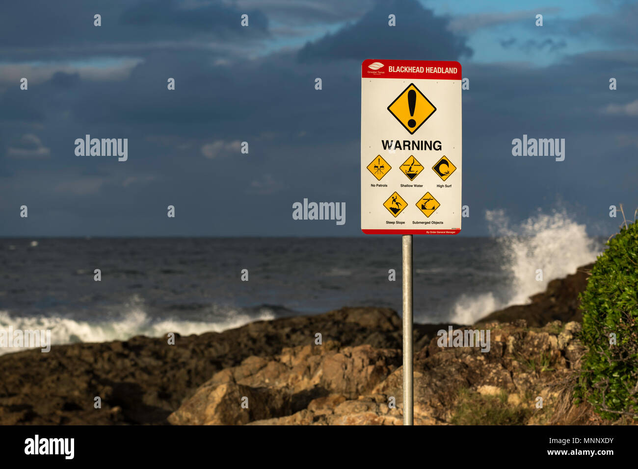 A sign on rocky outcrop near an Australian beach warning of surf hazards including hidden rocks, rips and unpredictable waves. Surf in the background - Stock Image