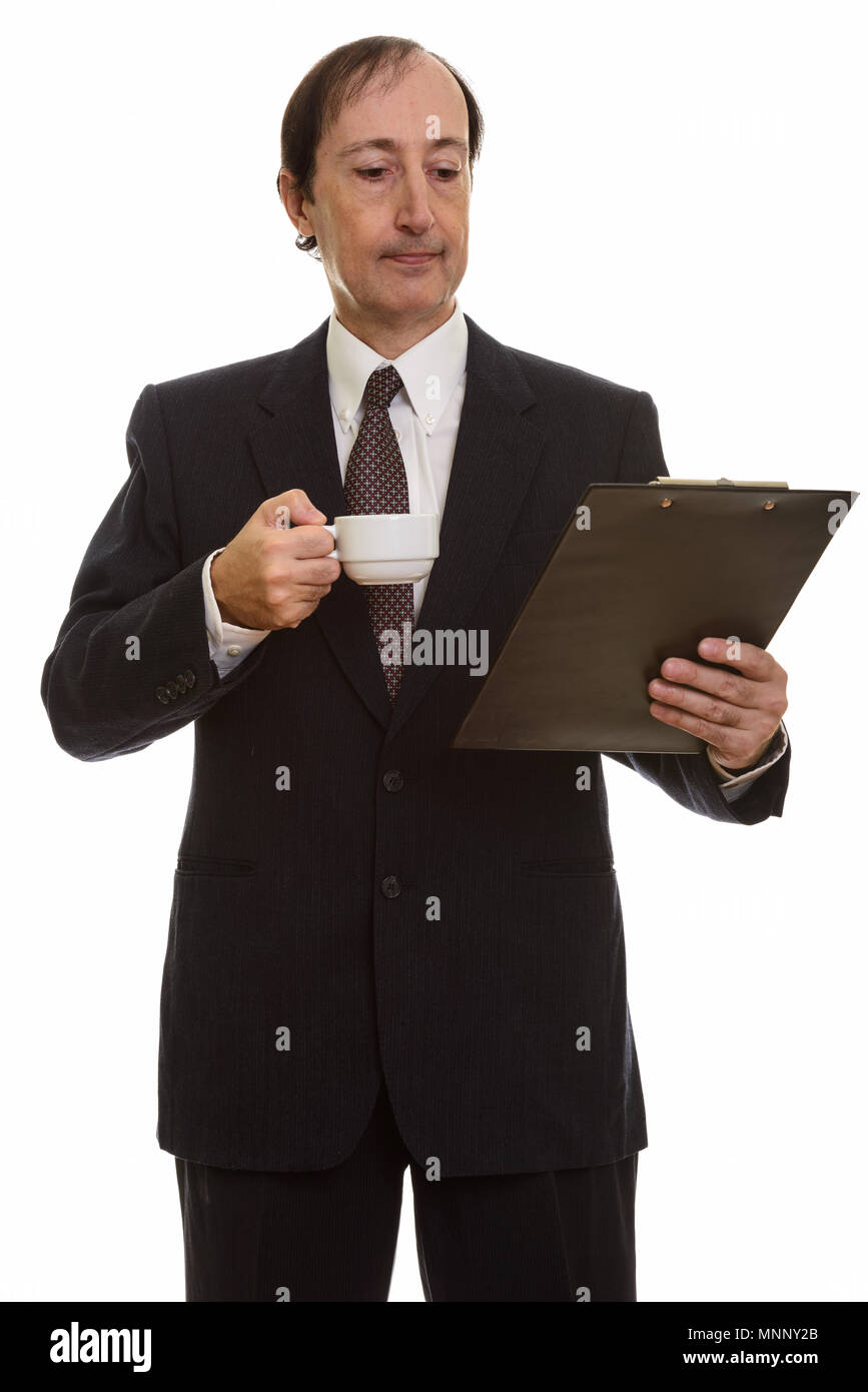 Studio shot of mature businessman holding coffee cup while readi - Stock Image