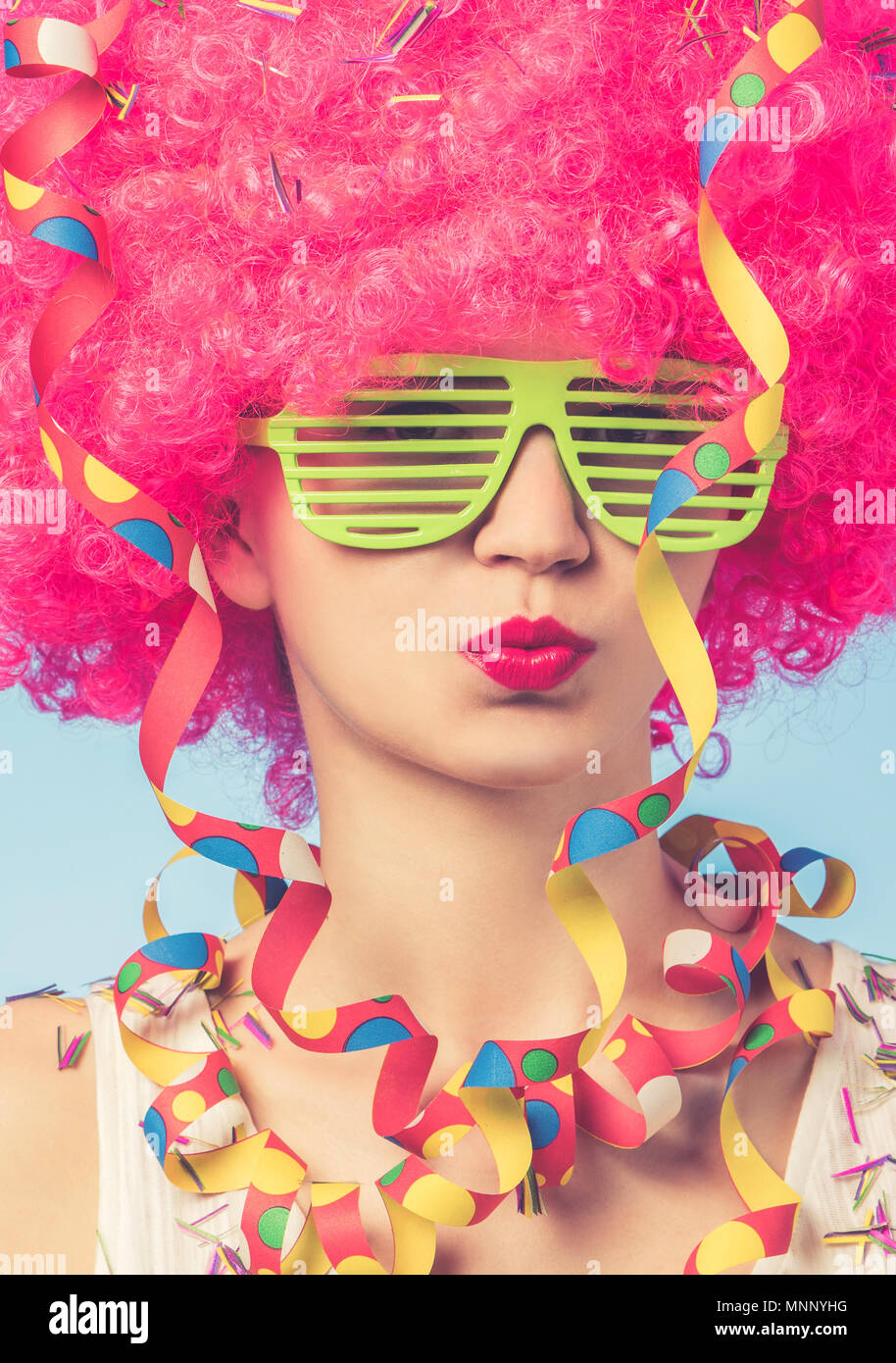 Portrait of beautiful woman in pink wig and green glasses with copy space - Stock Image