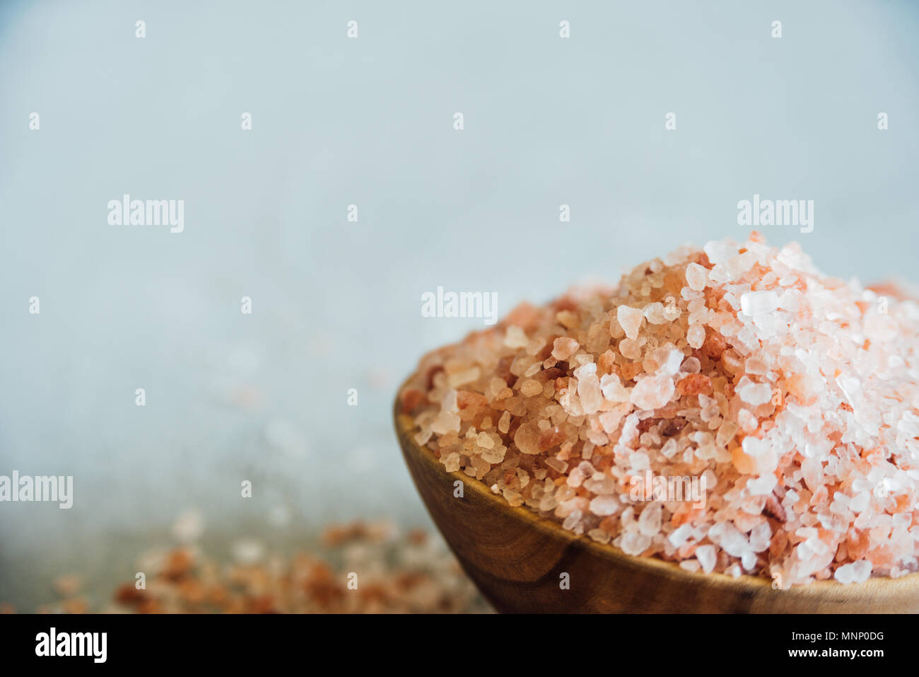 Wooden bowl with pink salt on neutral background - Stock Image