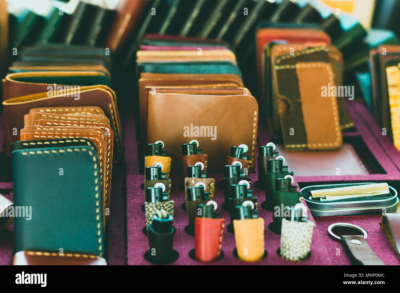 Colorful stack of leather lighters and wallets - Stock Image