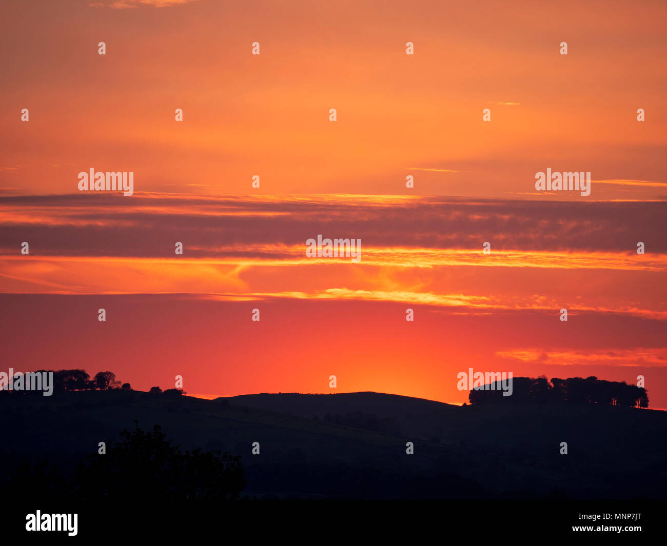 Peak District, Derbyshire, UK. 18th May, 2018. UK Weather: spectacular sunset over the ancient woods Hazleton Clump Cairn near Thorpe taken from Ashbourne Derbyshire, Peak District National Park Credit: Doug Blane/Alamy Live News Stock Photo