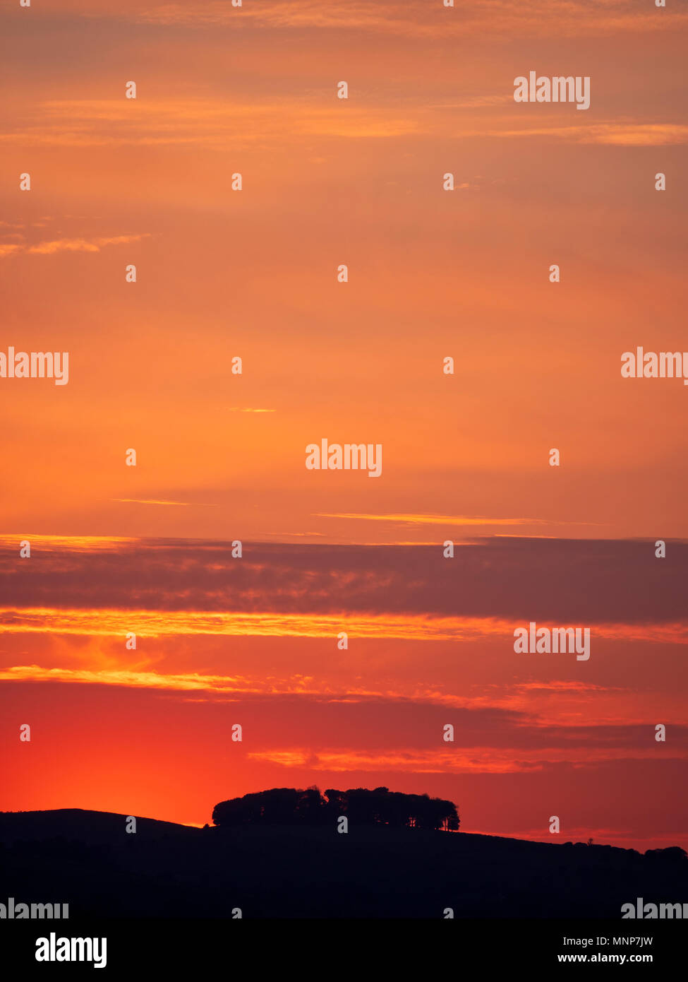 Peak District, Derbyshire, UK. 18th May, 2018. UK Weather: spectacular sunset over the ancient woods Hazleton Clump Cairn near Thorpe taken from Ashbourne Derbyshire, Peak District National Park Credit: Doug Blane/Alamy Live NewsStock Photo