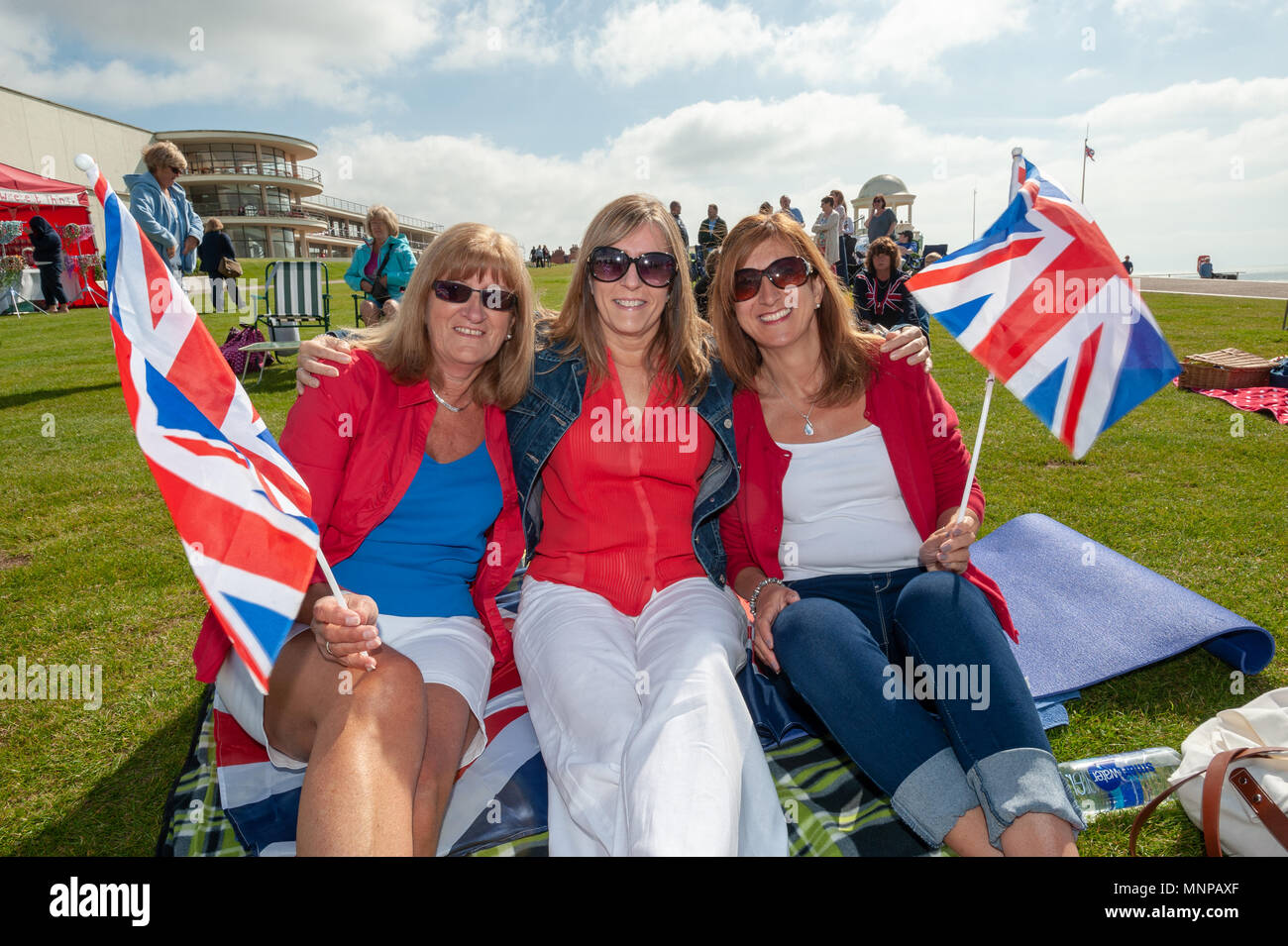 People wave Union Jack flags and celebrate Prince Harry and Meghan Markle's wedding at a Royal wedding event on the seafront in Bexhill On Sea, East Sussex, UK, England. Stock Photo