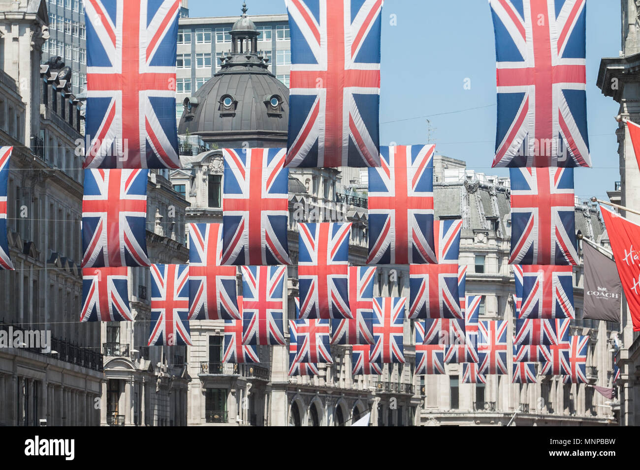 London UK. 19th May 2018. Tourists pose with a flag featuring Prince Harry  and