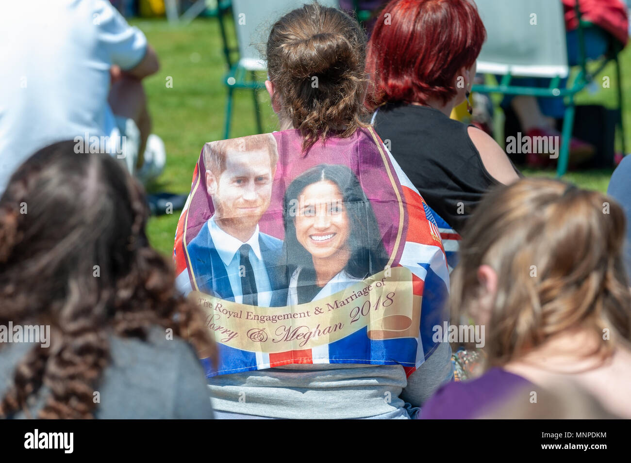 A person with a flag with the faces of Prince Harry and Meghan Markle on it at a Royal wedding event in Bexhill On Sea, East Sussex, England. Stock Photo