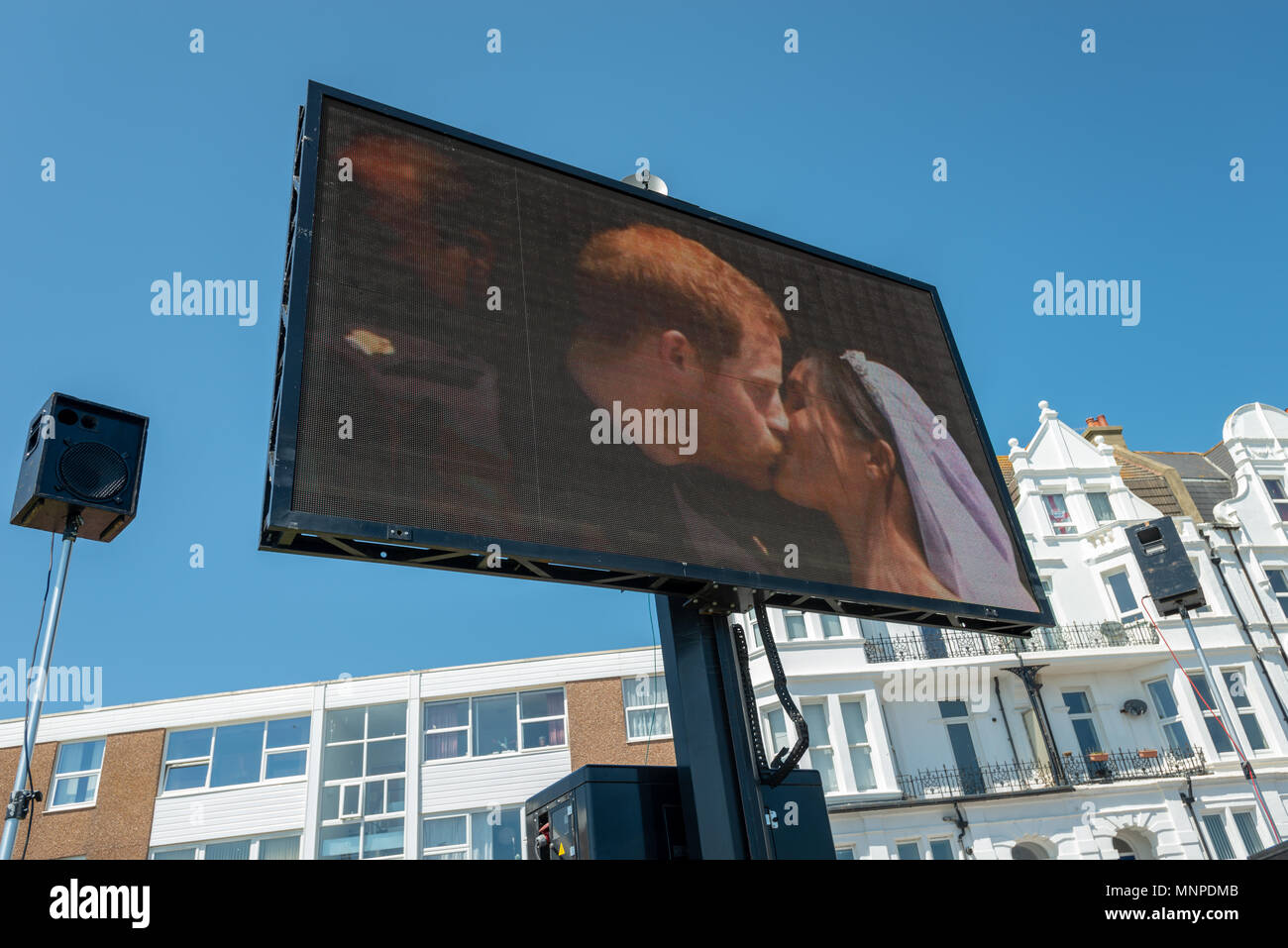 Displayed on a big screen on the seafront at a royal wedding celebration at Bexhill On Sea in East Sussex, England, Prince Harry and Meghan Markle kiss during their Royal wedding. Stock Photo