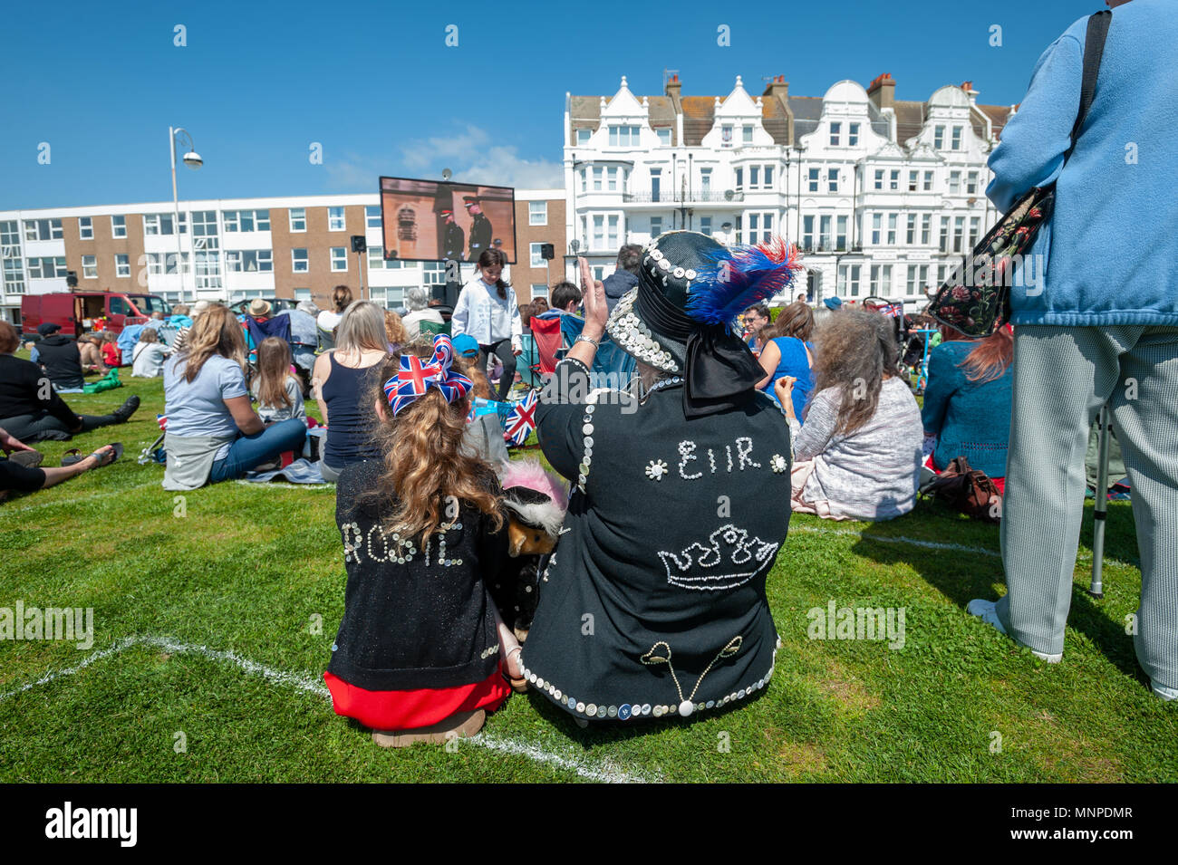 Dressed as Pearly Queens, a grandmother and her granddaughter cheer while watching Prince Harry and Meghan Markle's wedding on a big screen at a Royal wedding event at Bexhill On Sea in East Sussex, England. - Stock Image