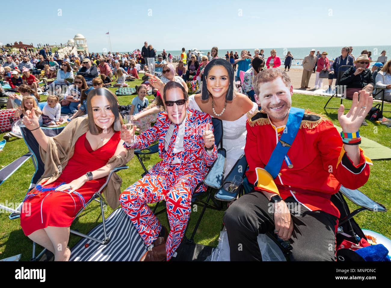 Couples wearing Prince William, Kate Middleton, Prince Harry and Meghan Markle masks, celebrate Prince Harry and Meghan Markle's wedding at a Royal wedding event on the seafront at Bexhill On Sea, East Sussex, UK. Stock Photo