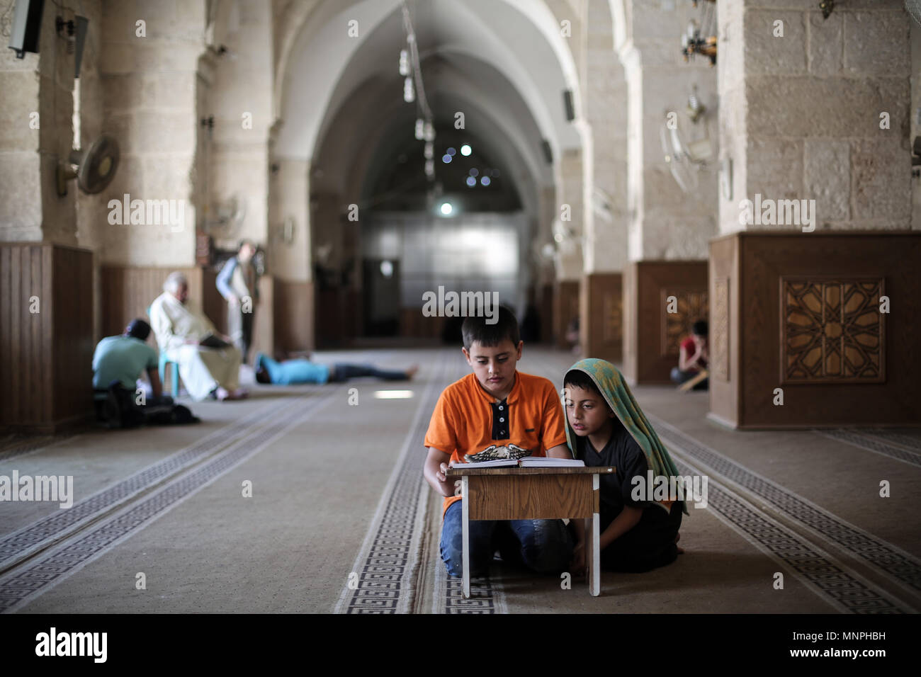 Idlib, Syria. 18th May, 2018. Syrian children who have been evacuated from the rebel-held area of Homs, read verses of Quran, Islam's holy book, at the Great Mosque of Maarat al-Numaan during the holy fasting month of Ramadan, near Idlib, Syria, 18 May 2018.Ramadan is the ninth and holiest month of the Islamic calendar in which Muslims from all over the world refrain from eating, drinking and smoking from dawn to dusk. Credit: Anas Alkharboutli/dpa/Alamy Live News - Stock Image