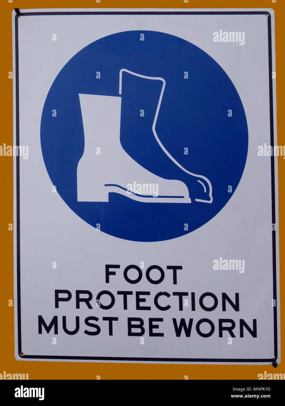 A danger sign warning that protection must be worn for feet - Stock Image