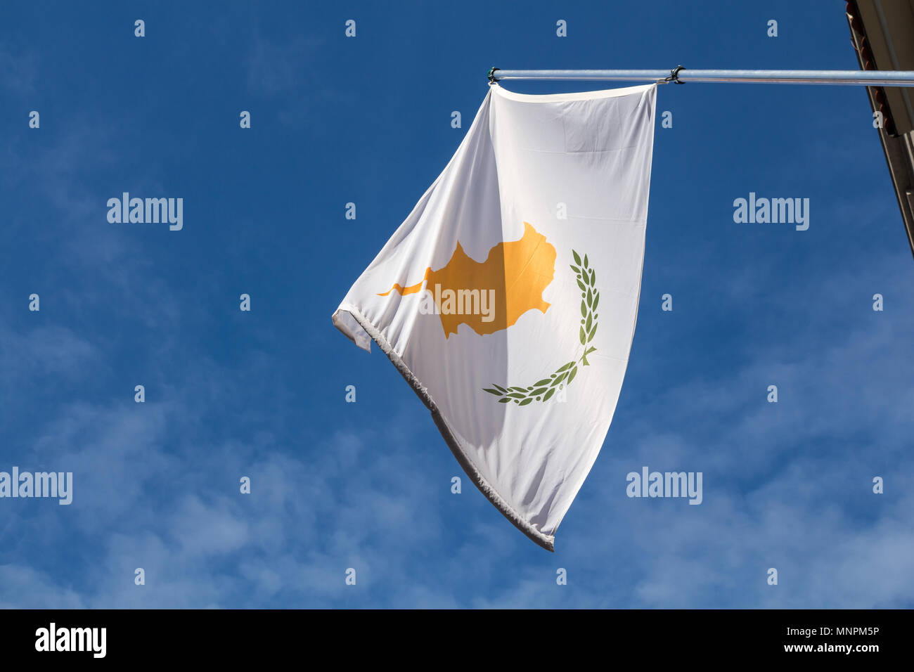 Cyprus flag on the pole hanging from a house in the street. Blue sky with white clouds. - Stock Image