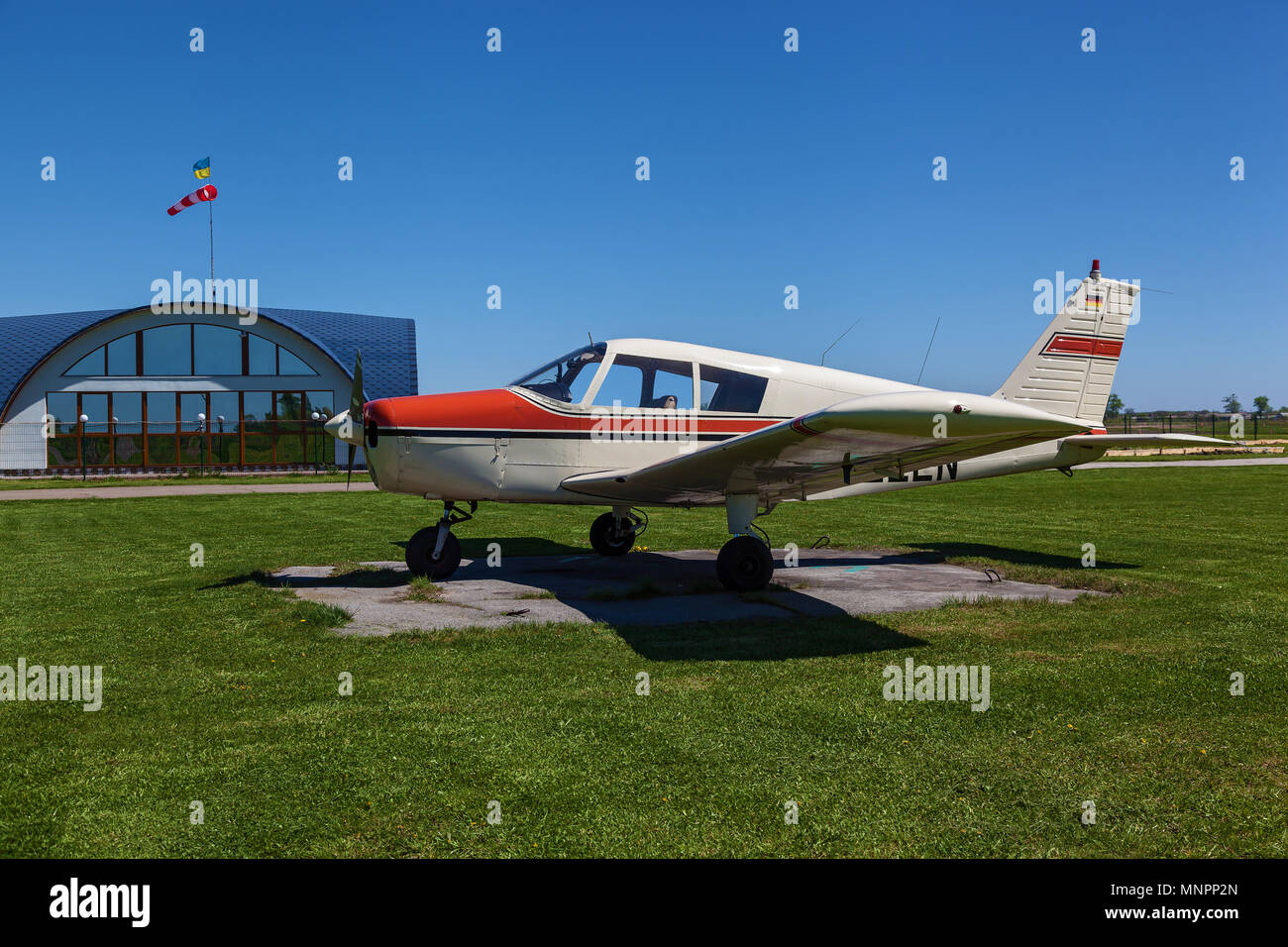 The plane Piper Cherokee stands on the green grass on a