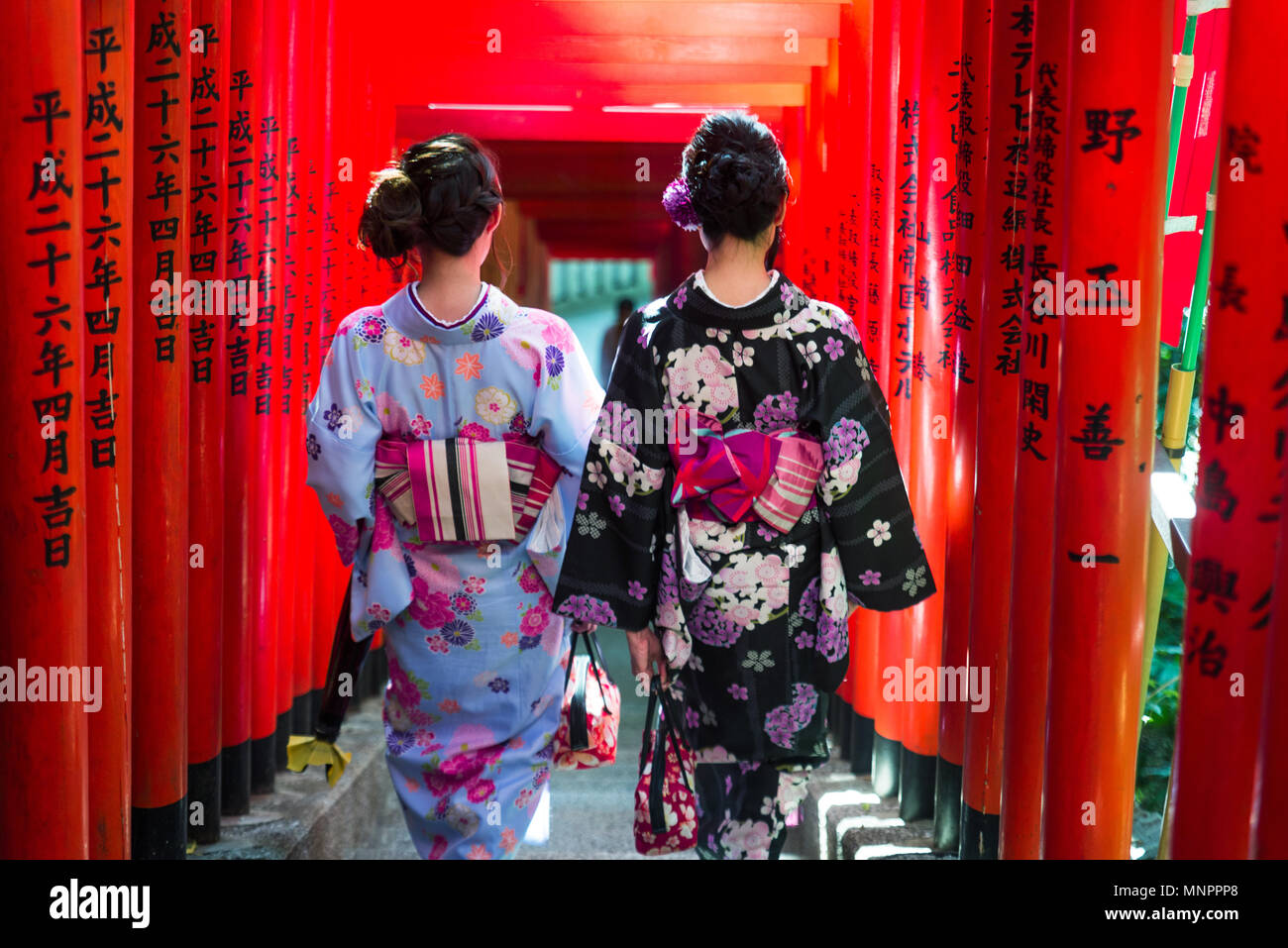 Two beautiful girls with traditional dress walking outdoors - Stock Image