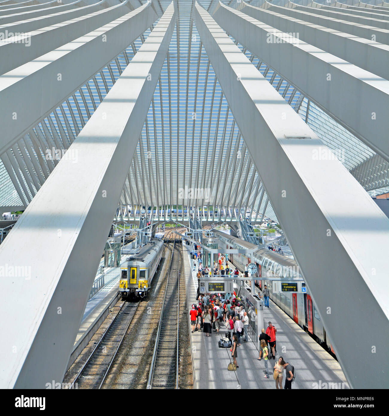 Aerial or birds eye view from above looking down on busy train station platform group of people waiting in modern public transport building glass roof - Stock Image
