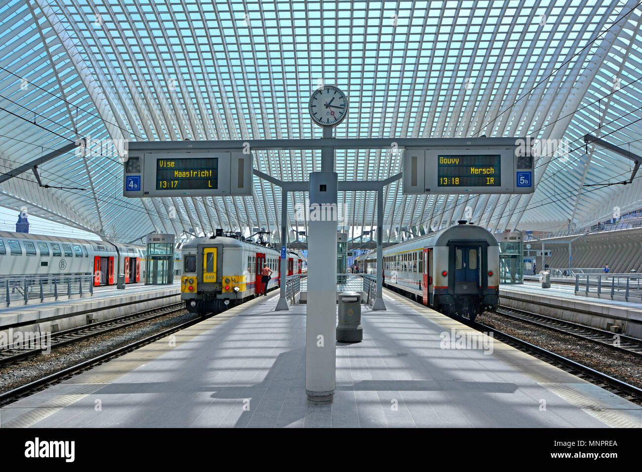 Symmetrical architecture balance of modern public transport Liege Belgium EU train station railway platform clock & large glass roof covering trains - Stock Image