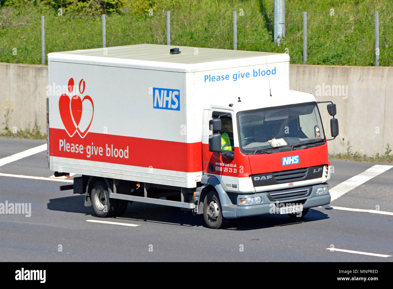 Daf lorry truck & driver M25 motorway side advertising donate give blood National Health Service in England NHS Blood and Transplant service or NHSBT - Stock Image