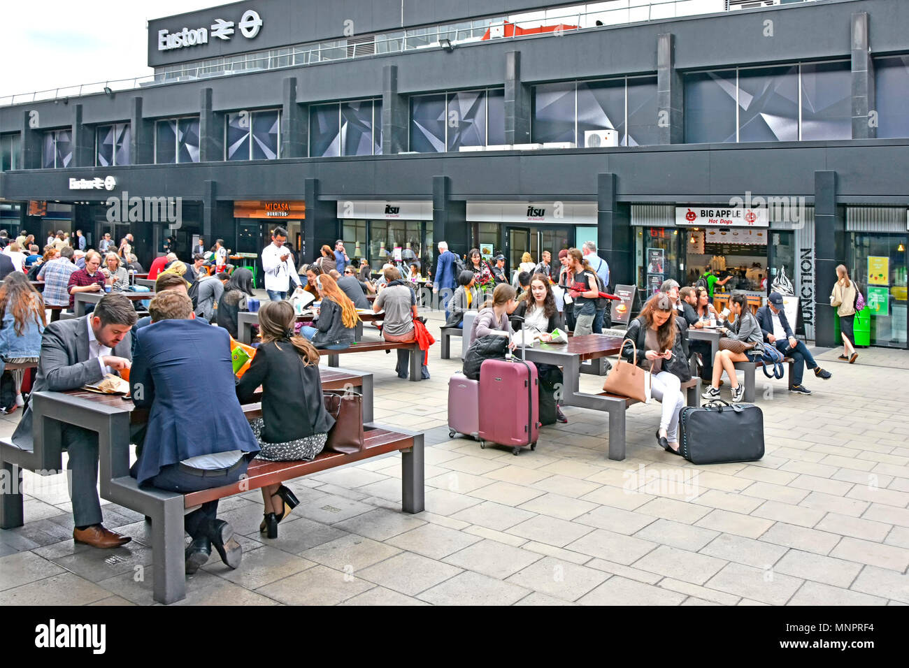 Crowd of people   railway travel wait at picnic table outside London Euston train station some with suitcase luggage fast food café shops beyond UK - Stock Image